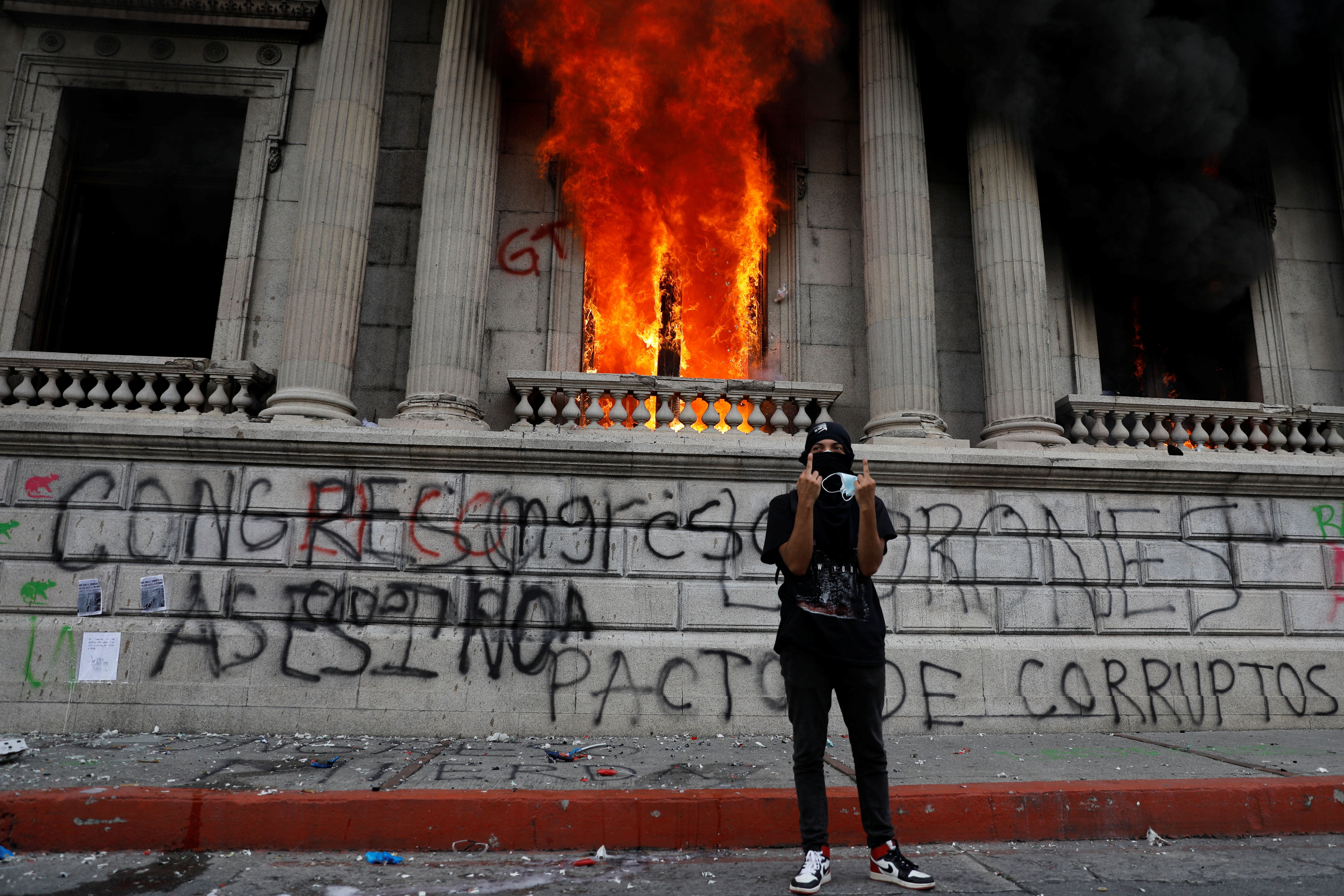 A demonstrator gestures after demonstrators set an office of the Congress building on fire during a protest demanding the resignation of President Alejandro Giammattei, in Guatemala City, Guatemala November 21, 2020.