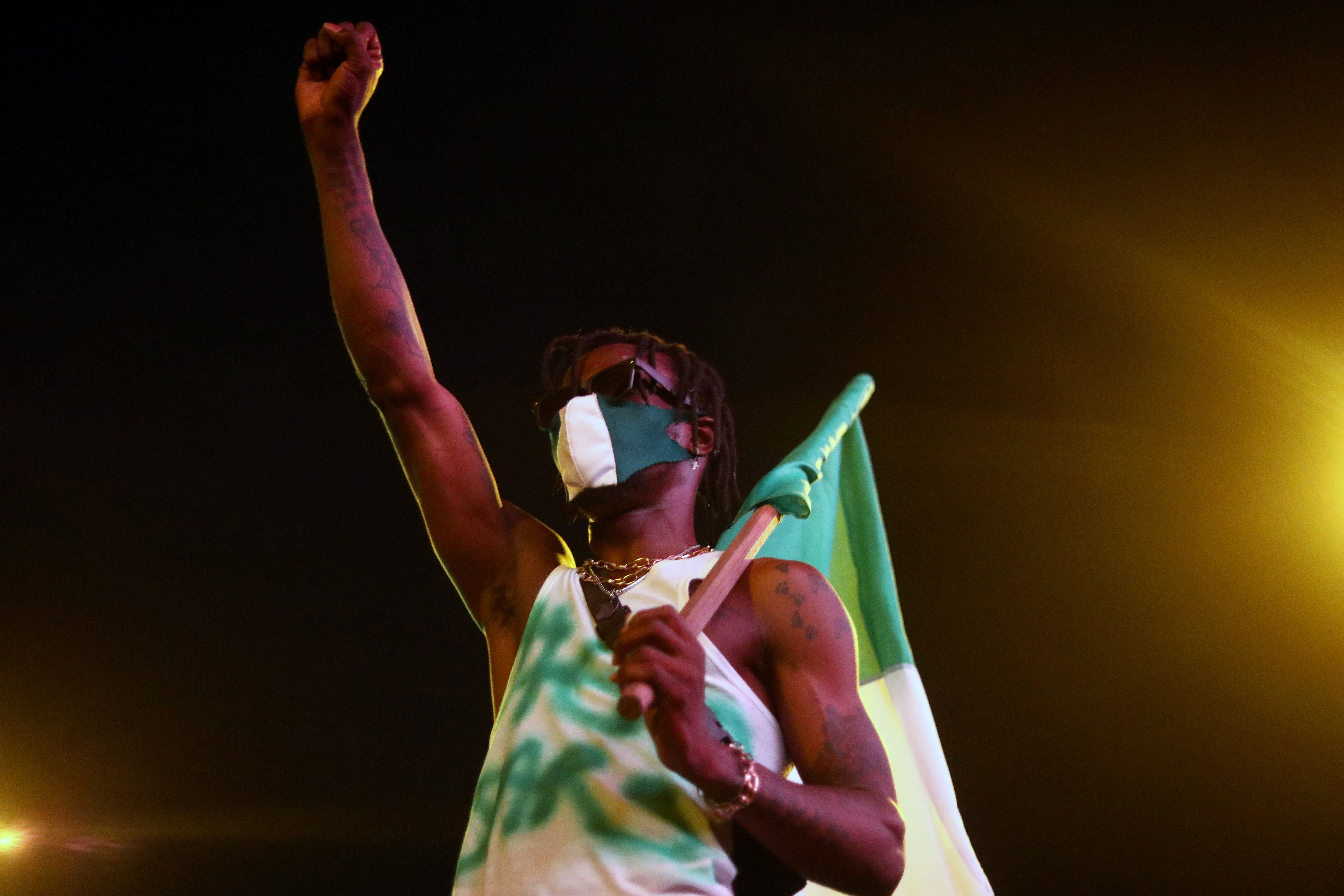 A demonstrator gestures as he holds the Nigerian flag during protest against alleged police brutality in Lagos. Reuters