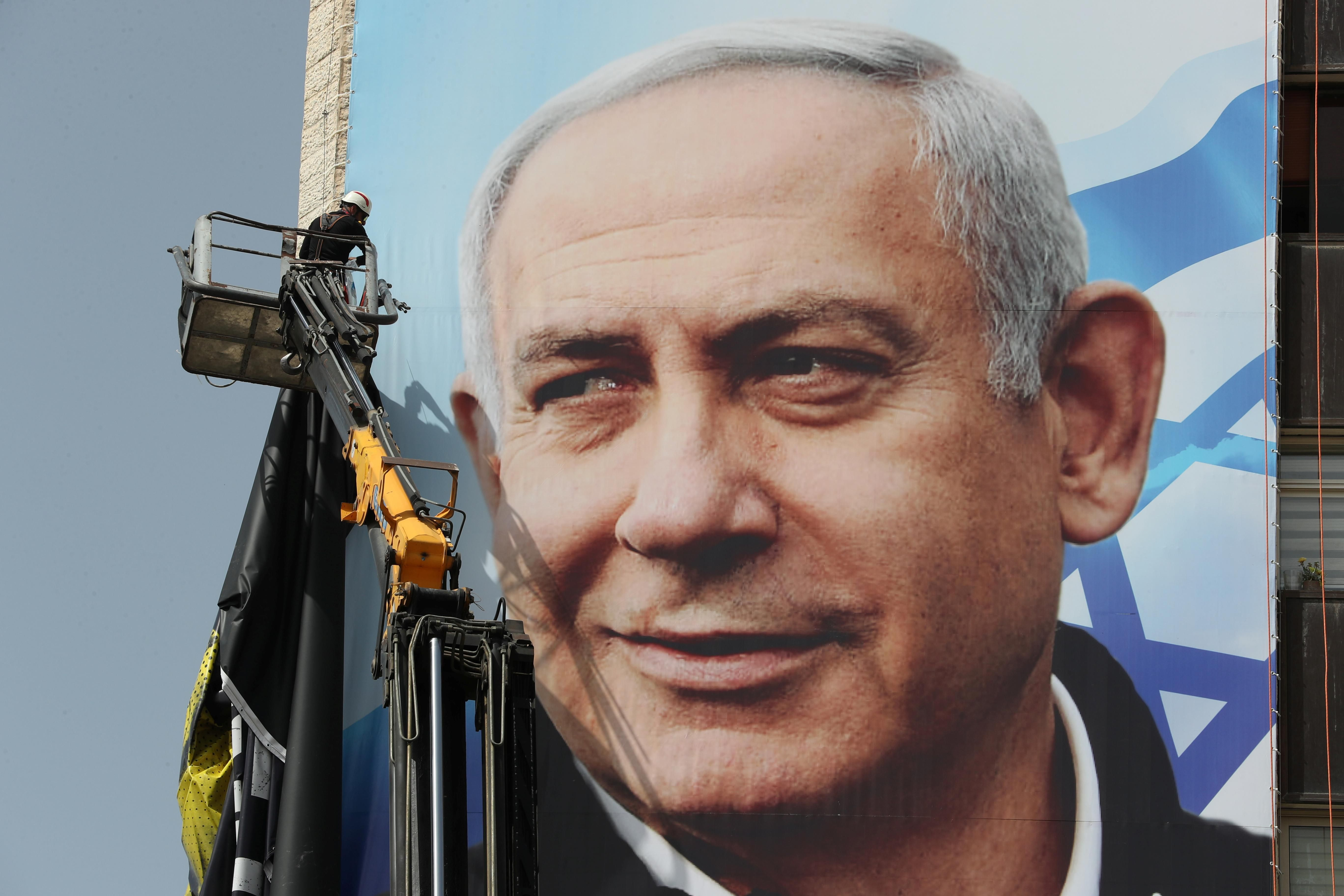 A labourer hangs a Likud party election campaign banner depicting party leader Israeli Prime Minister Benjamin Netanyahu, ahead of a March 23 ballot, in Jerusalem March 10, 2021.
