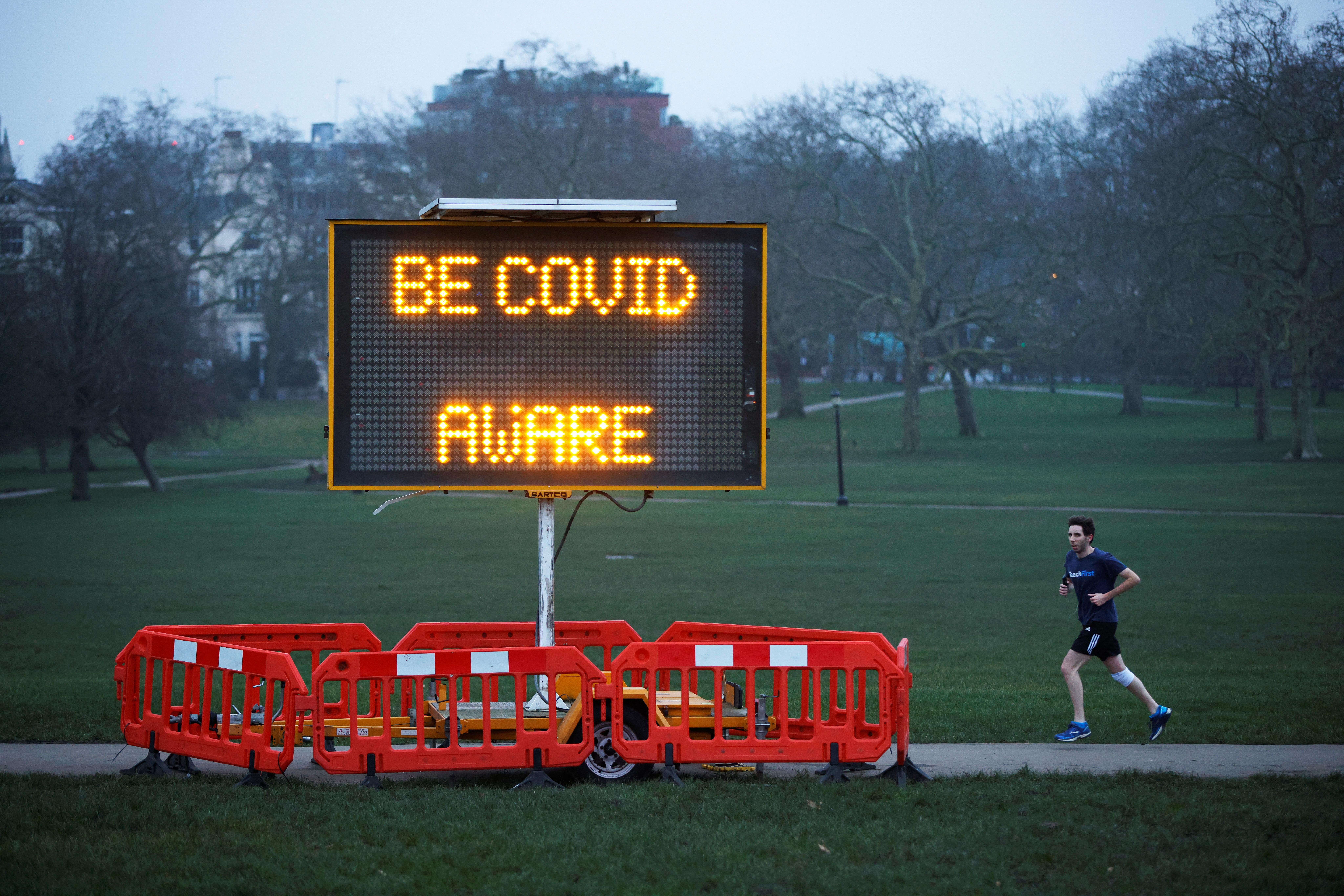 A man jogs past a public health information sign at dawn on the first day of 2021 on Primrose Hill amid the coronavirus disease (COVID-19) outbreak, in London, Britain January 1, 2021