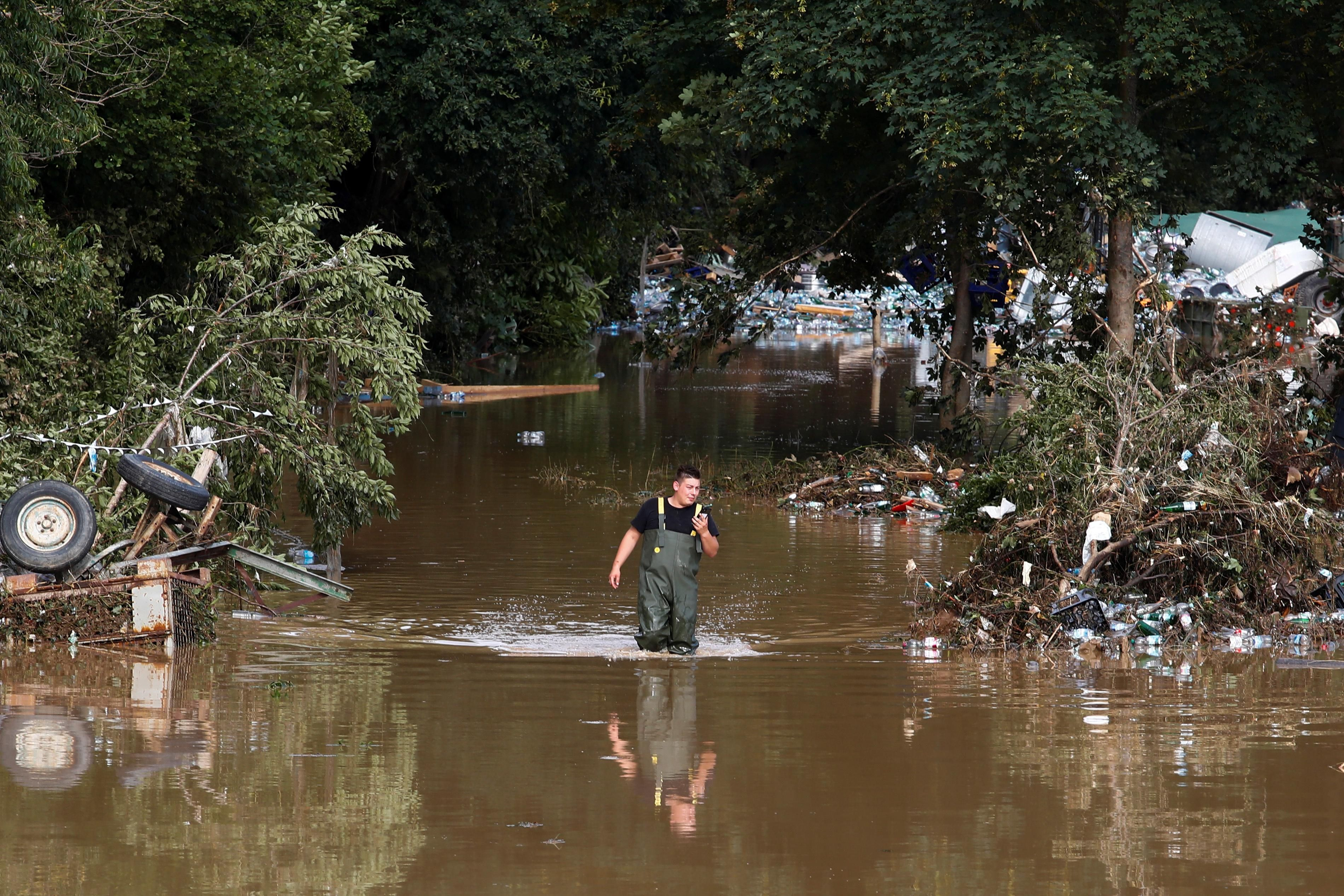 A man walks through the water in an area affected by floods following heavy rainfalls in Bad Neuenahr-Ahrweiler, Germany, July 15, 2021