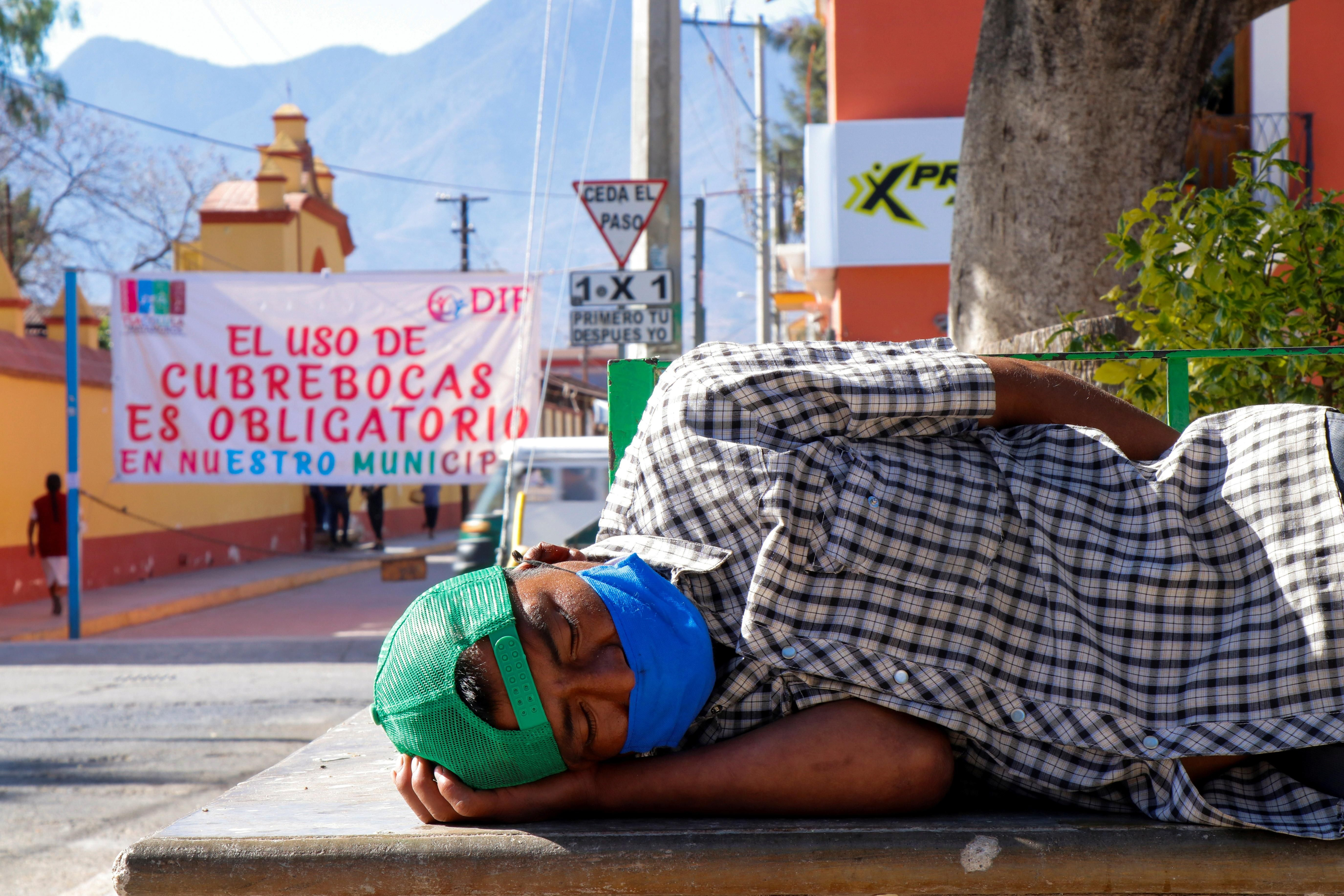 """A man wearing a face mask sleeps at a park near a banner reading """"The use of face masks is mandatory in our municipality"""", amid the coronavirus disease (COVID-19) pandemic, in Tlacolula de Matamoros, Oaxaca state, Mexico January 30, 2021."""