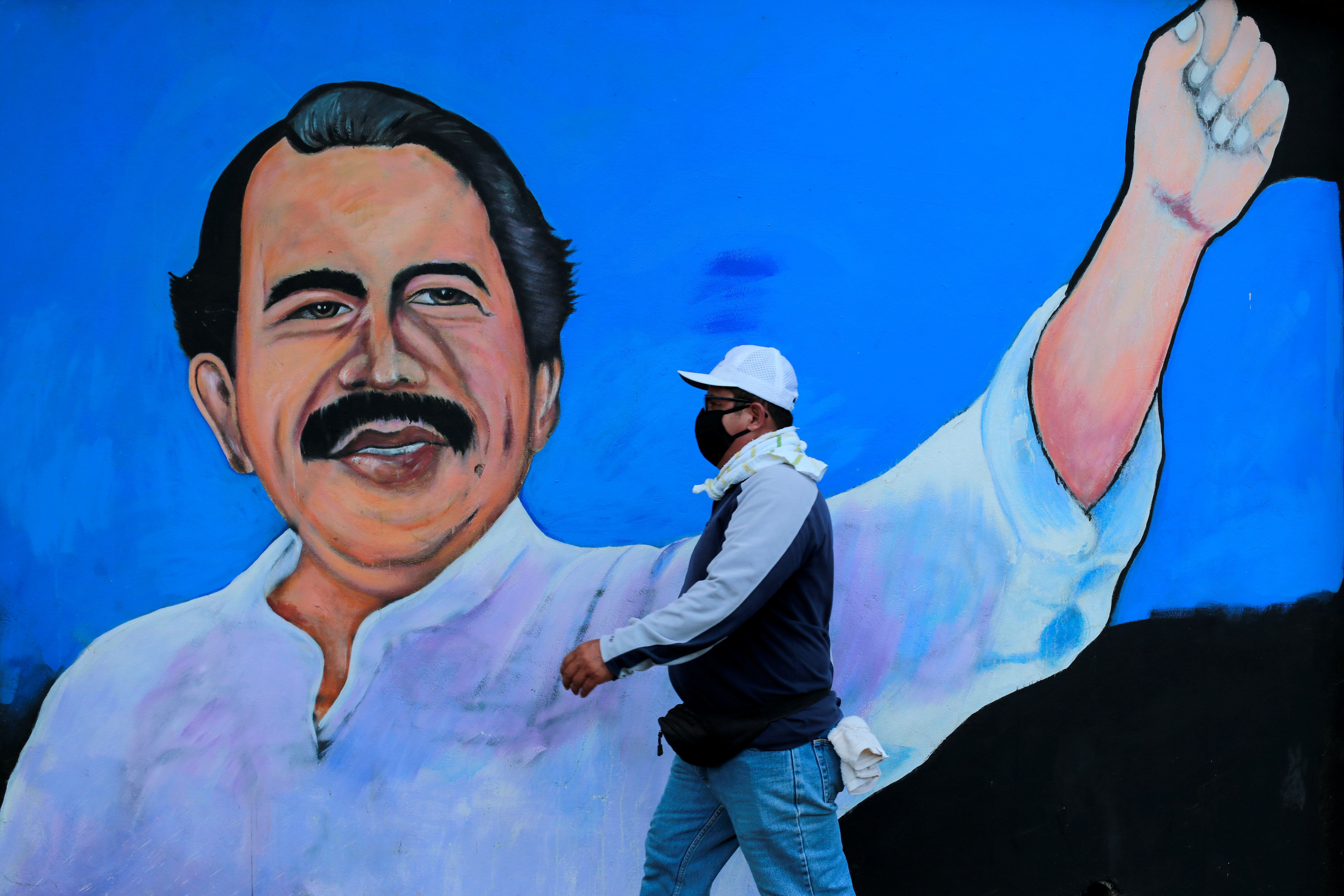 A man wearing a face mask to protect himself from COVID-19 walks in front of a mural depicting Nicaraguan President Daniel Ortega in Managua. Reuters
