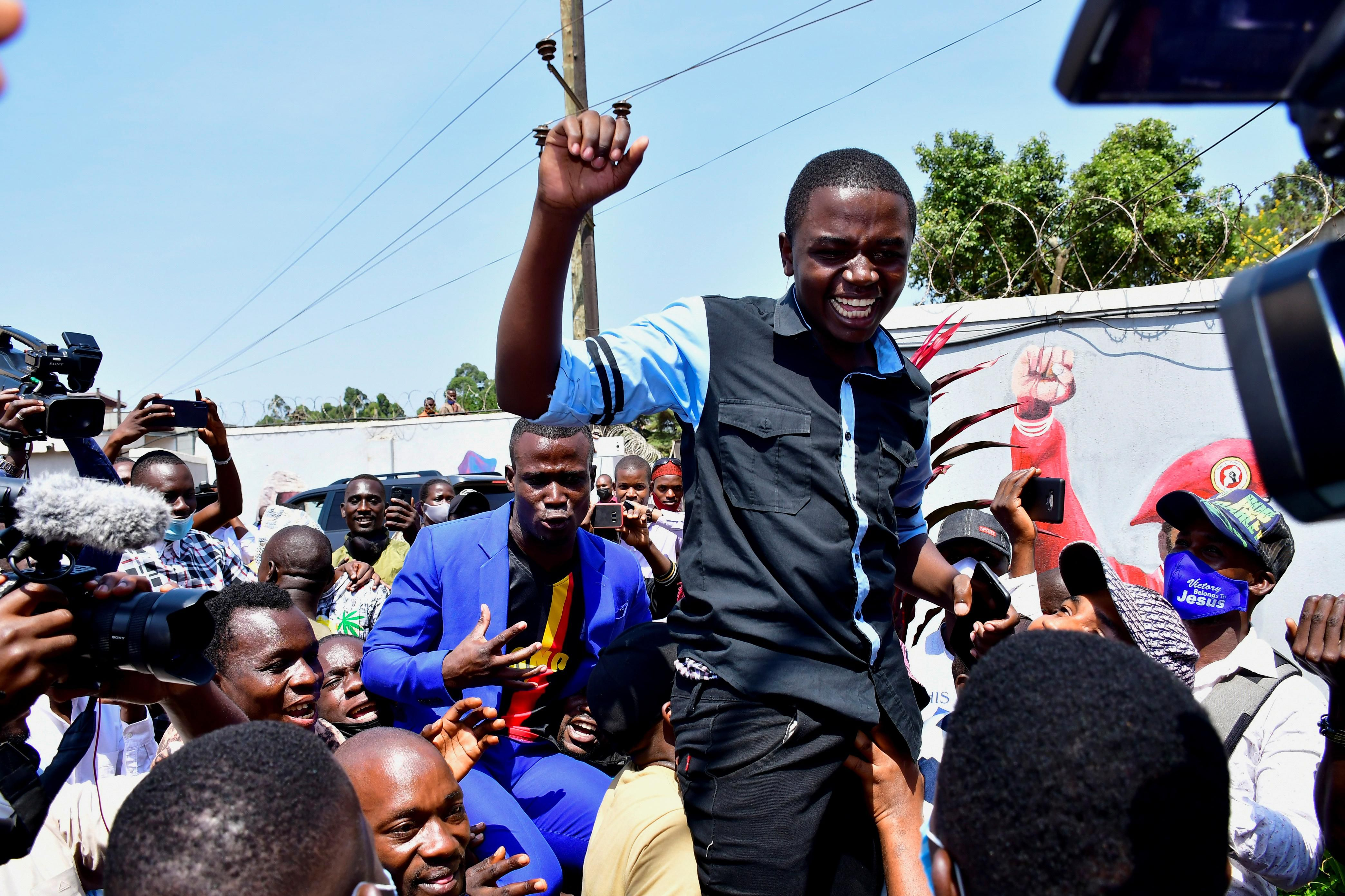 A member of former presidential candidate Robert Kyagulanyi also known as Bobi Wine's security detail celebrates after being released on bail, at the party's headquarters in Kampala, Uganda June 14, 2021.