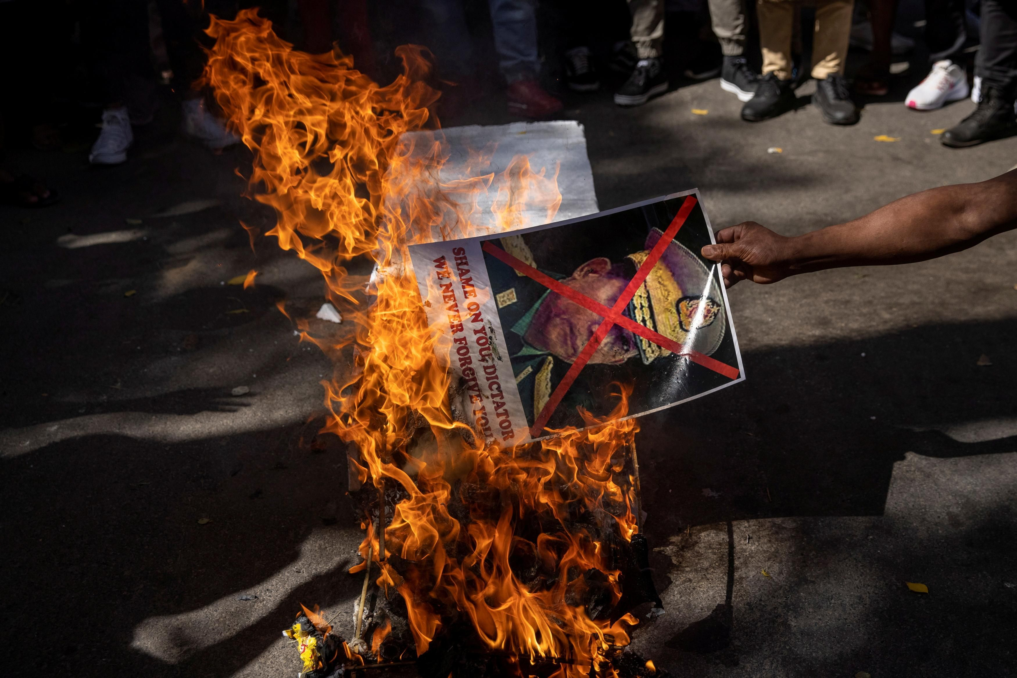 A Myanmar citizen living in India burns a poster of Myanmar's army chief Senior General Min Aung Hlaing with his face crossed out, during a protest organised by Chin Refugee Committee, against the military coup in Myanmar, in New Delhi, India, March 3, 2021.