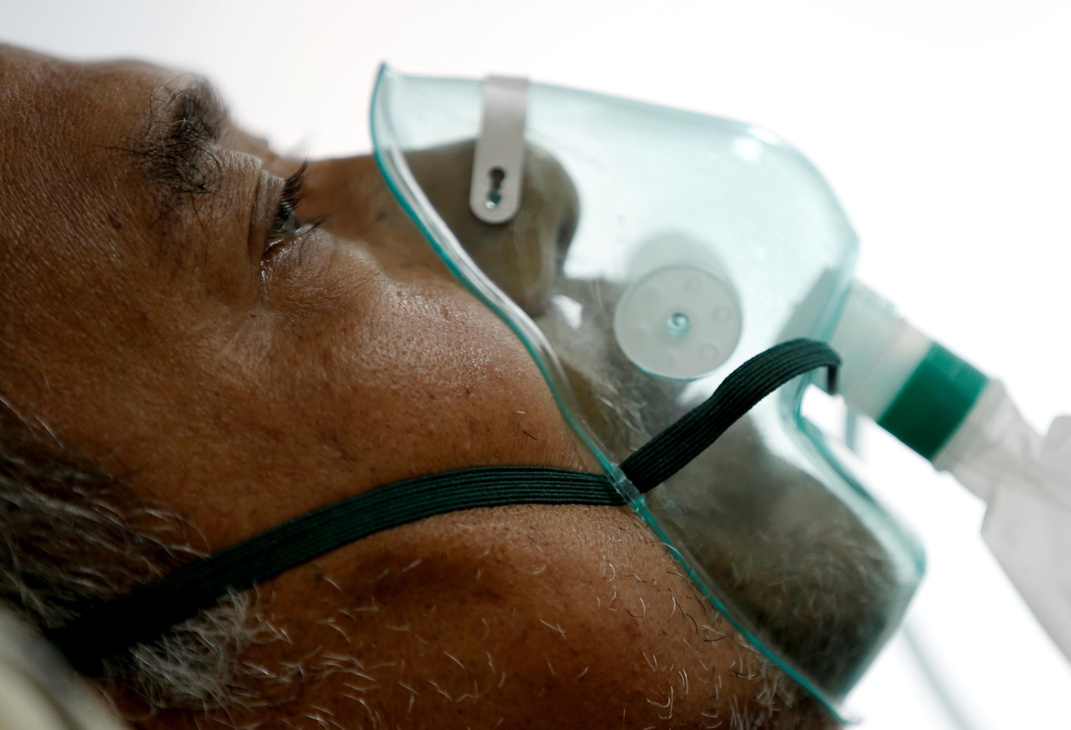 A patient suffering from the coronavirus disease (COVID-19) breathes with a non-rebreather mask in an isolation room at a hospital in Bogor, Indonesia January 26, 2021.