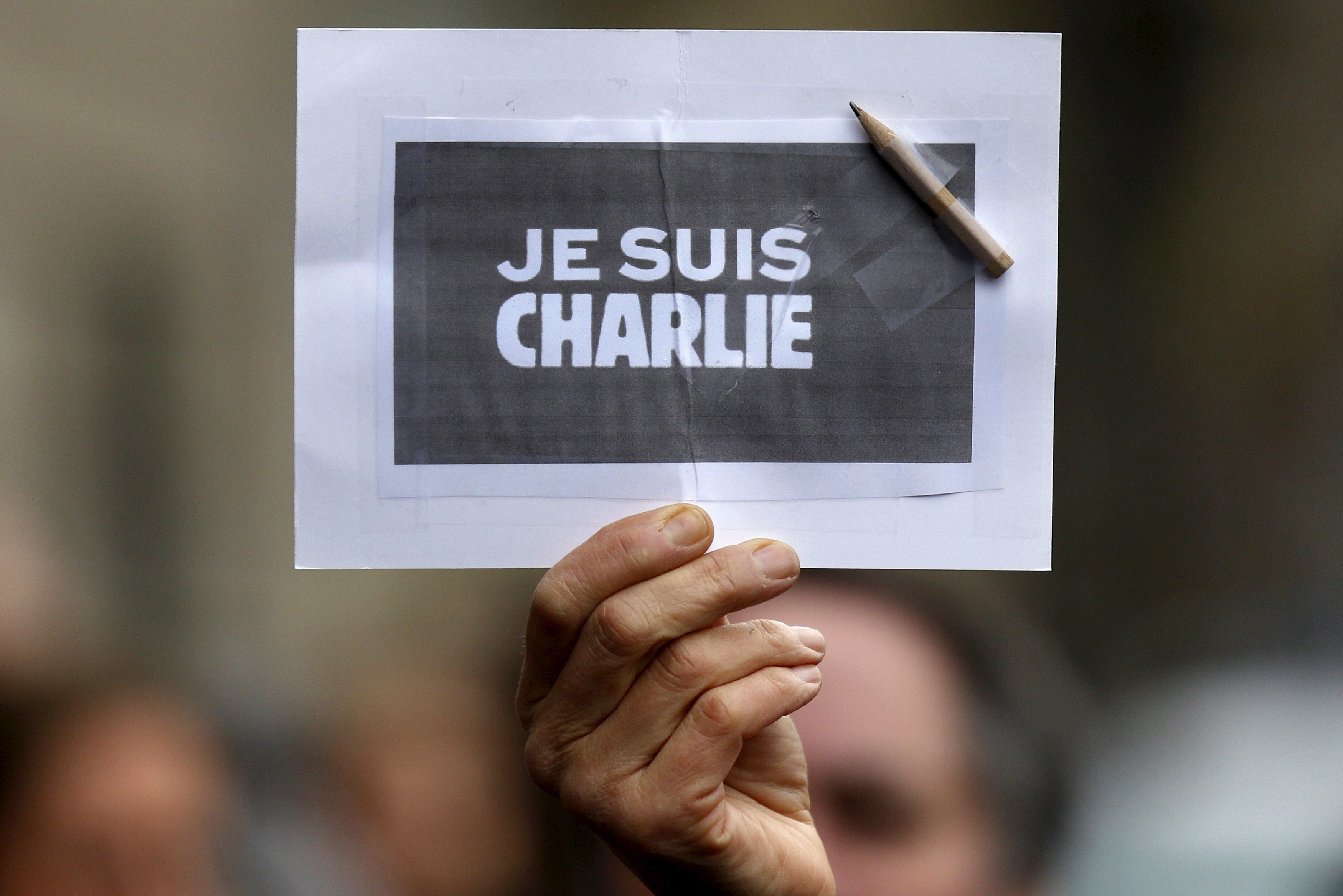 """A person holds a placard with a pencil which reads """"I am Charlie"""" during a minute of silence in Strasbourg for victims of the shooting at the Paris offices of Charlie Hebdo."""