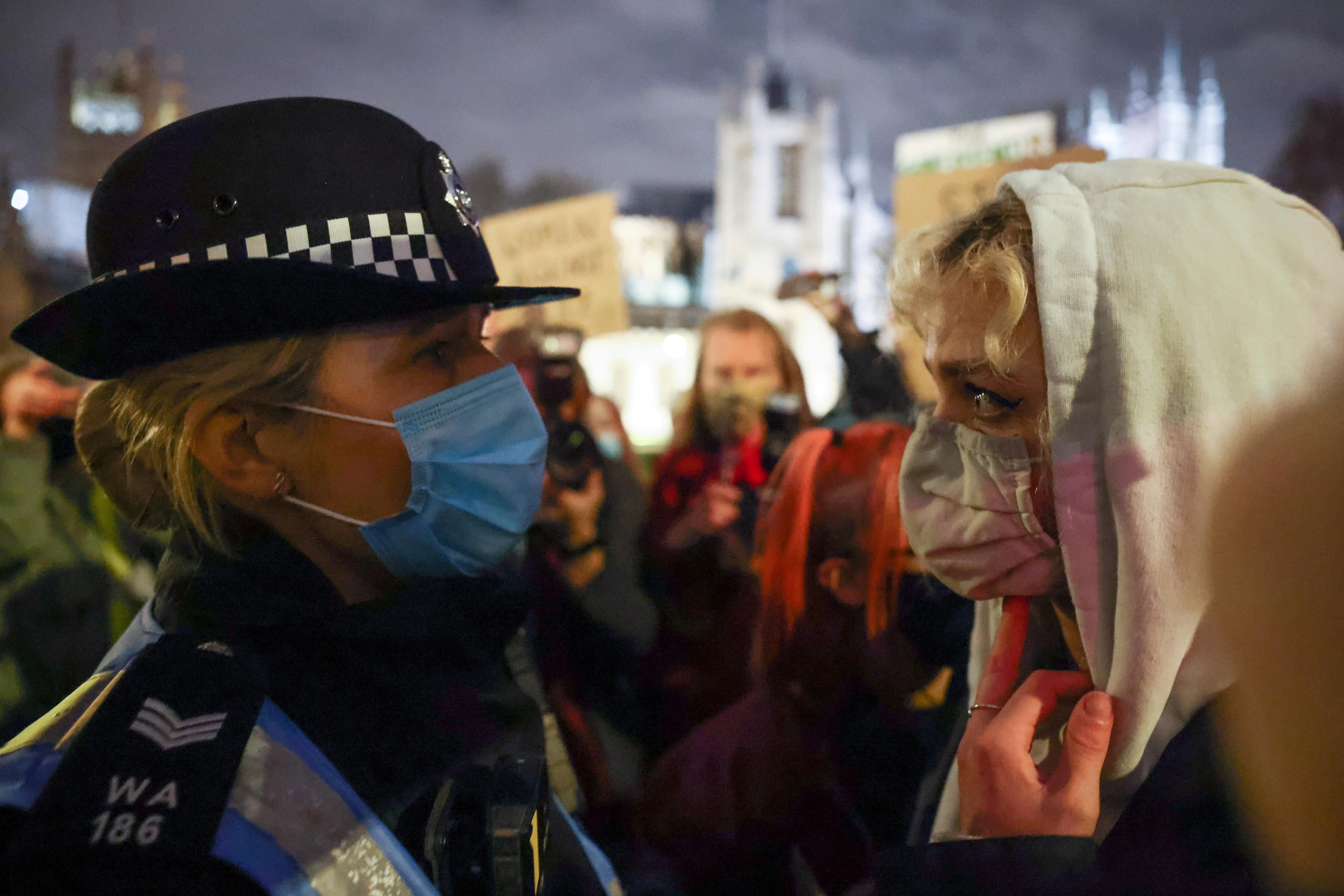A person stands in front of a police officer at the Parliament Square, following the kidnap and murder of Sarah Everard, in London, Britain March 14, 2021.