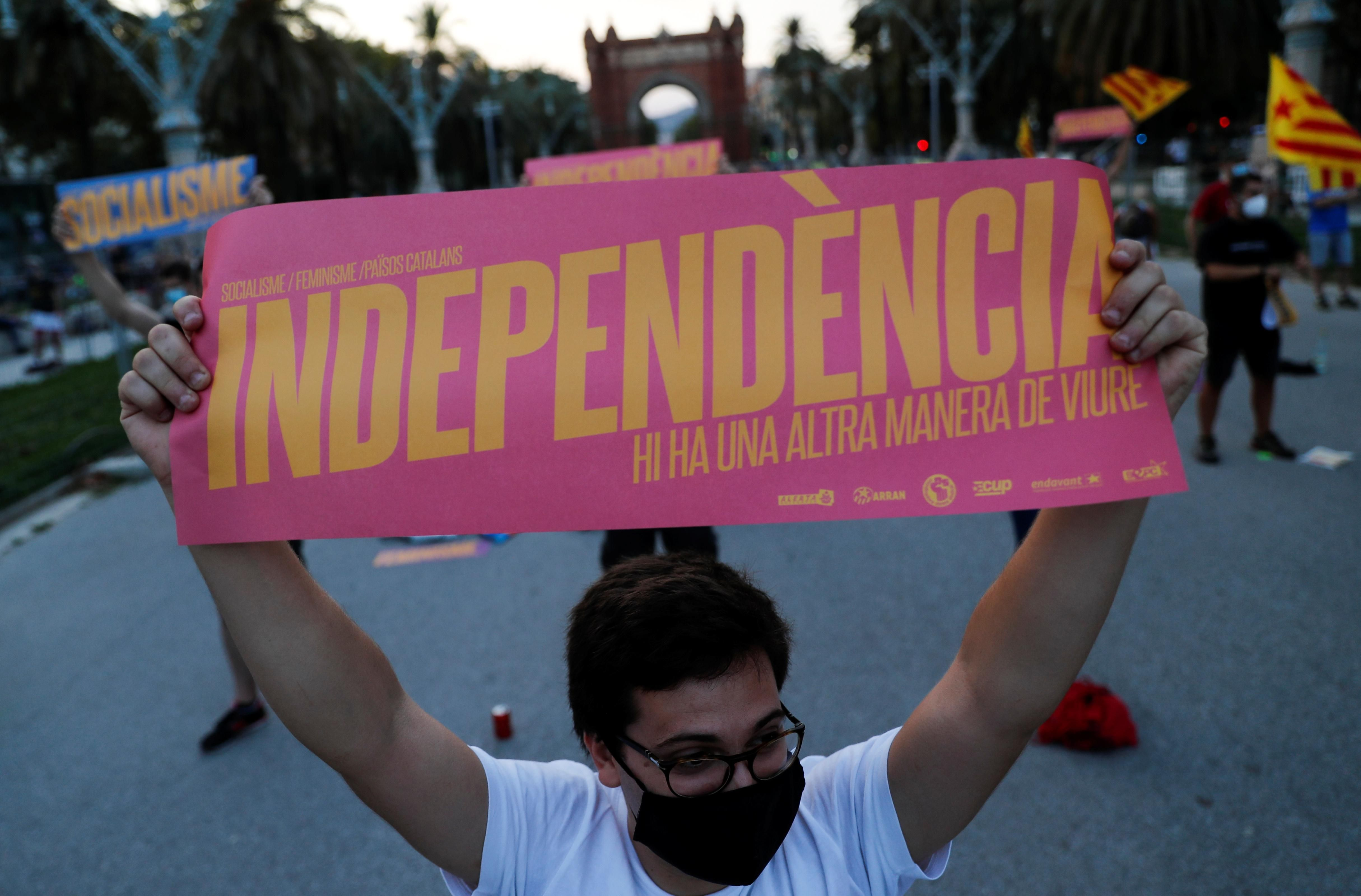 """A pro-independence protester holds a placard that reads: """"Independence. There's another way to live"""", during a demonstration on Catalonia's day of 'La Diada' in Barcelona, Spain, September 11, 2020"""