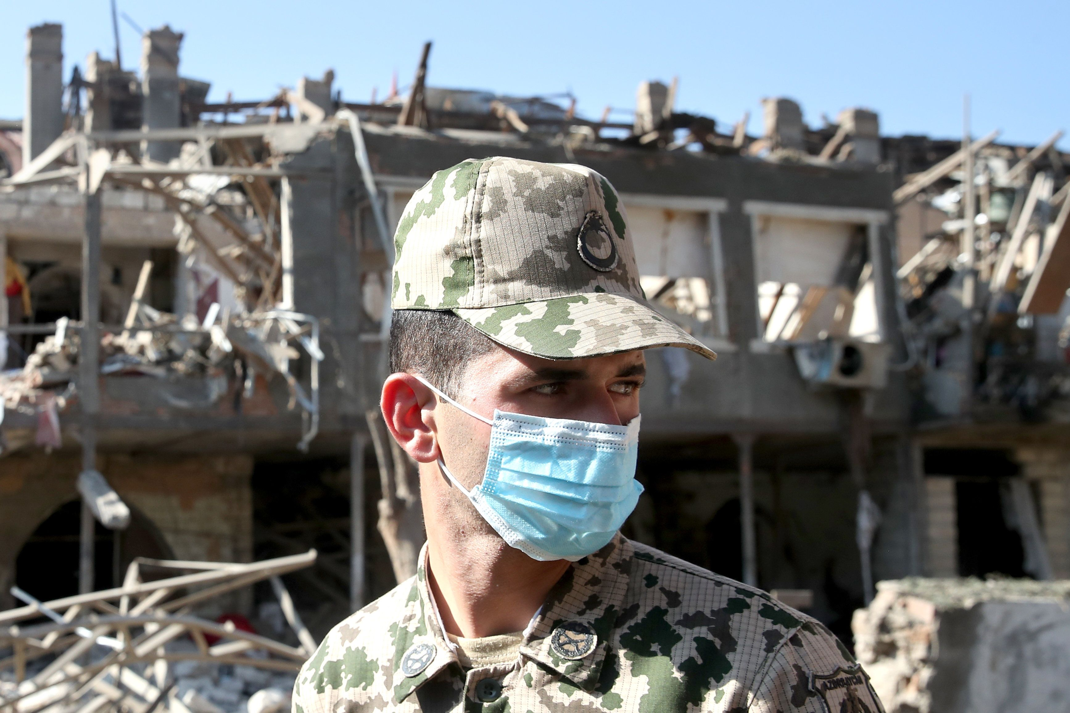 A serviceman examines a residential area of the city damaged in a rocket attack in Ganja, Azerbaijan on 11 October