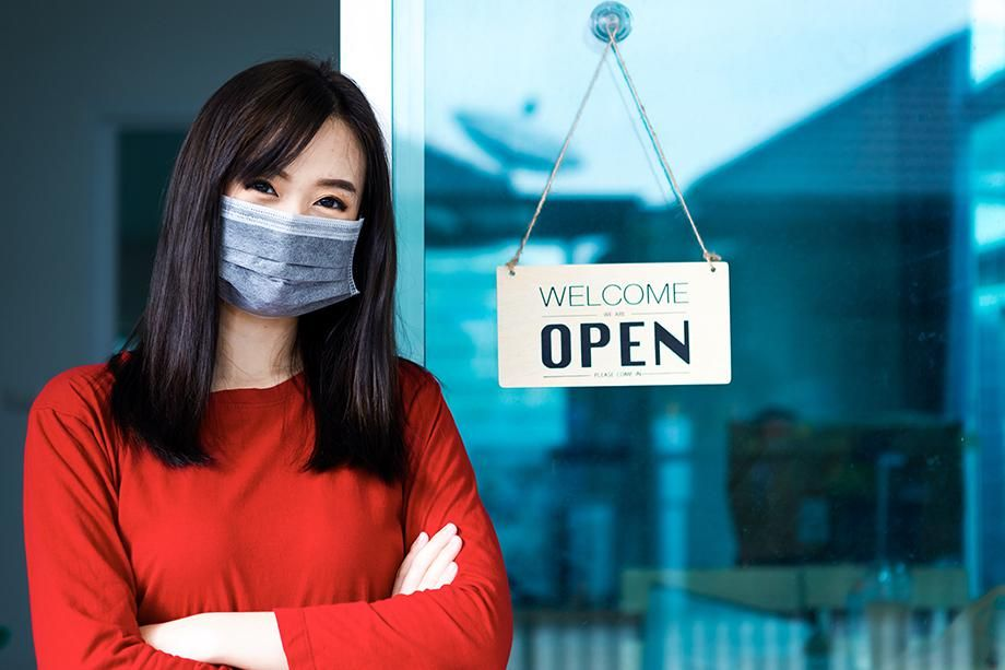 """A small business owner in front of a business with a """"welcome - open"""" sign"""
