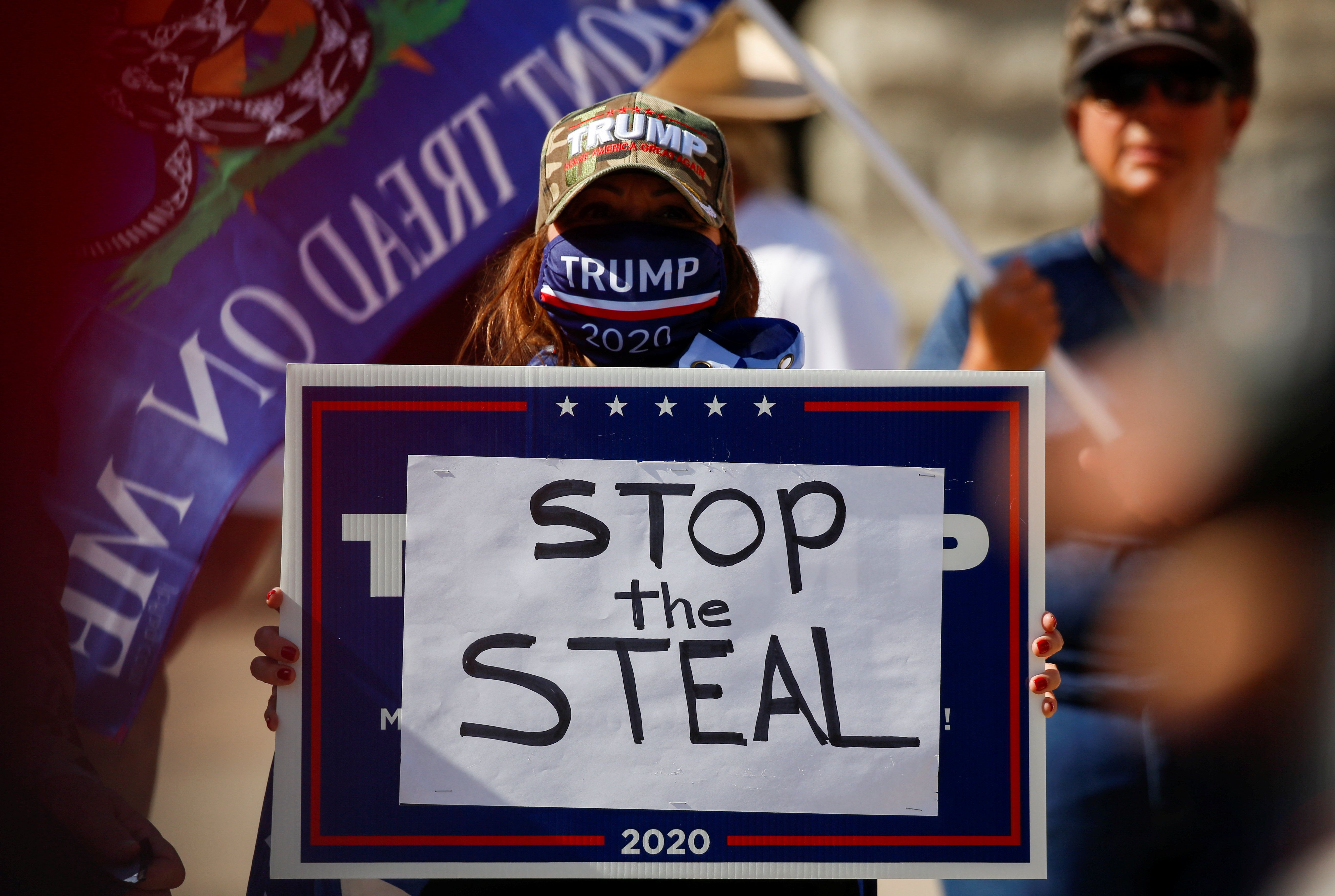 """A supporter of U.S. President Donald Trump holds a sign during a """"Stop the Steal"""" protest after the 2020 U.S. presidential election was called for Democratic candidate Joe Biden, in front of the Arizona State Capitol in Phoenix, Arizona"""