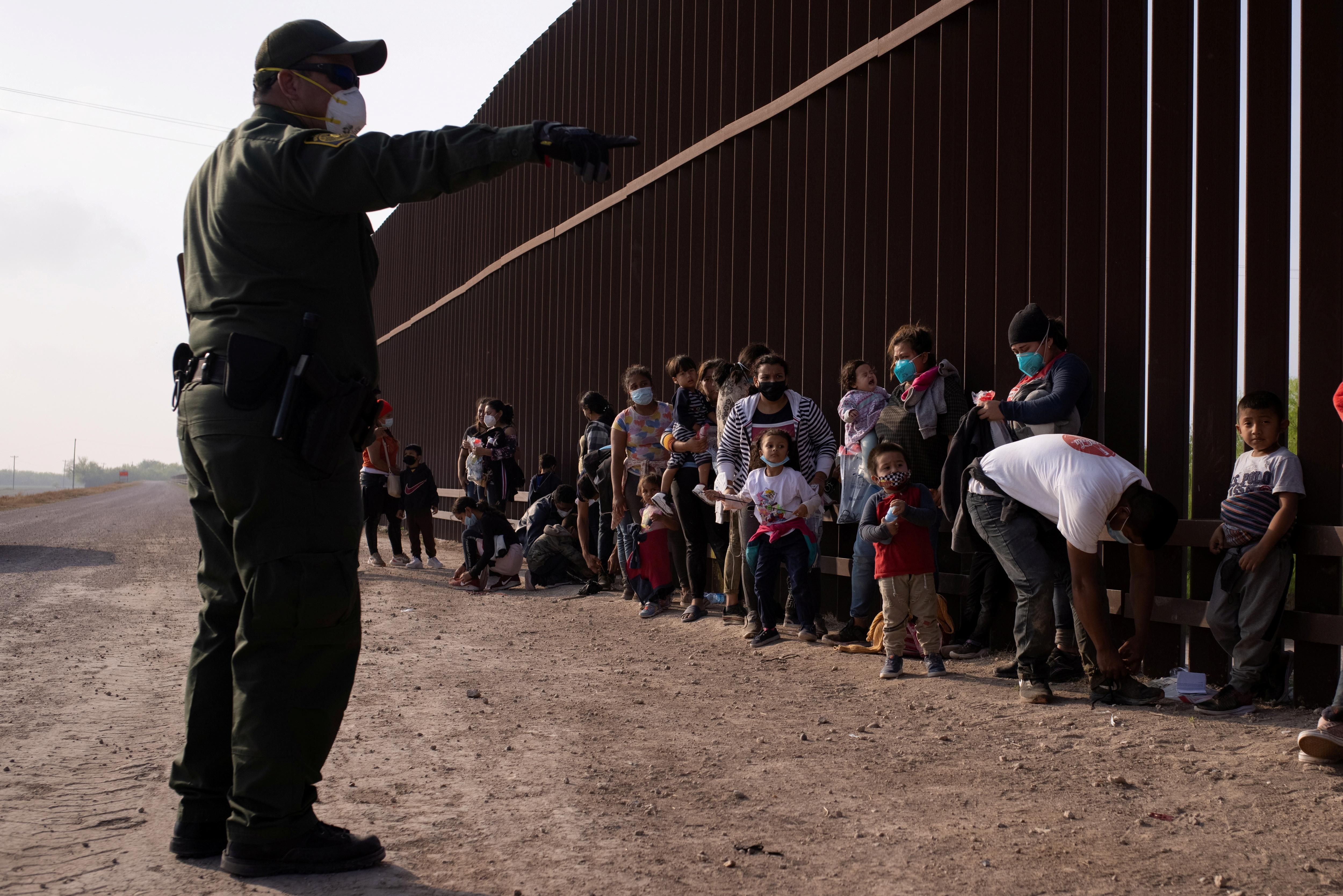 A U.S. Border Patrol agent instructs asylum-seeking migrants as they line up along the border wall after crossing the Rio Grande river into the United States from Mexico on a raft, in Penitas, Texas, U.S., March 17, 2021.