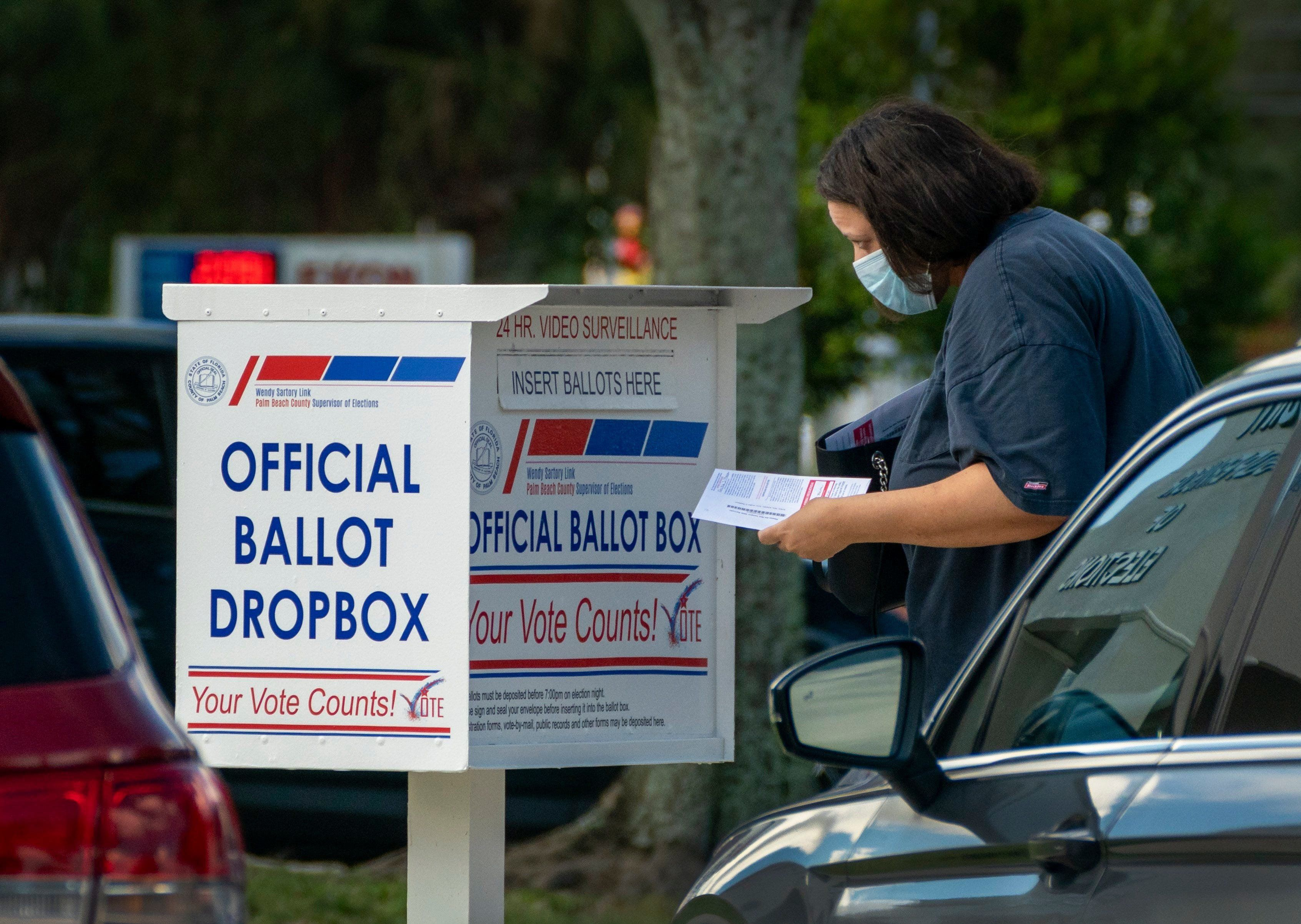 A voter drops off her vote by mail ballot at the Supervisor of Elections office on election day in West Palm Beach, Florida on August 18, 2020.