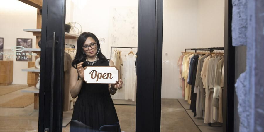 A woman holding an open sign inside a small business.