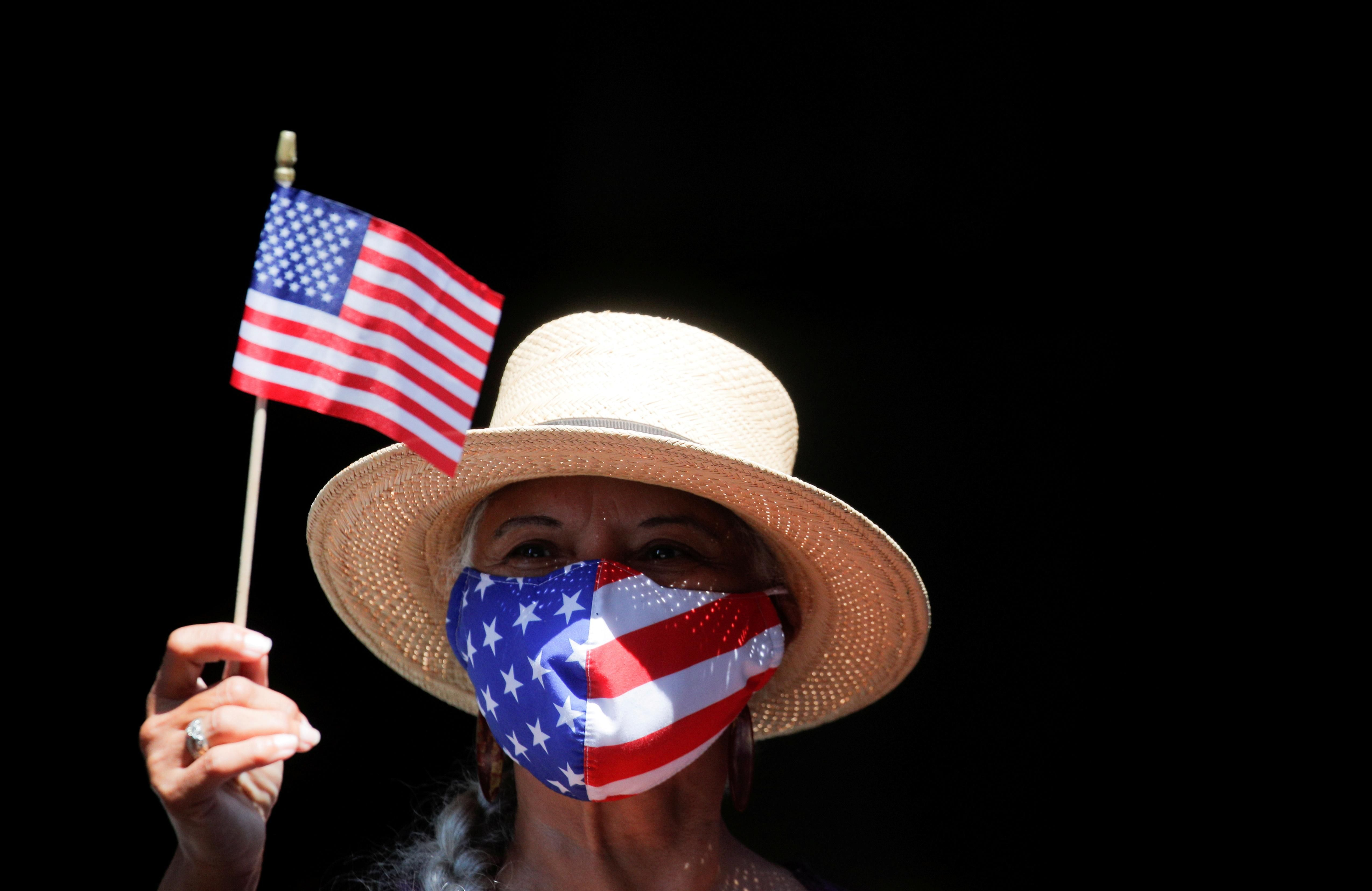 """A woman waves a small U.S. flag as she takes part in the Hometown Heroes ticker tape parade, to honor essential workers for their work during the outbreak of the coronavirus disease (COVID-19), up New York City's """"Canyon of Heroes"""" in lower Manhattan in New York City, New York, U.S., July 7, 2021"""