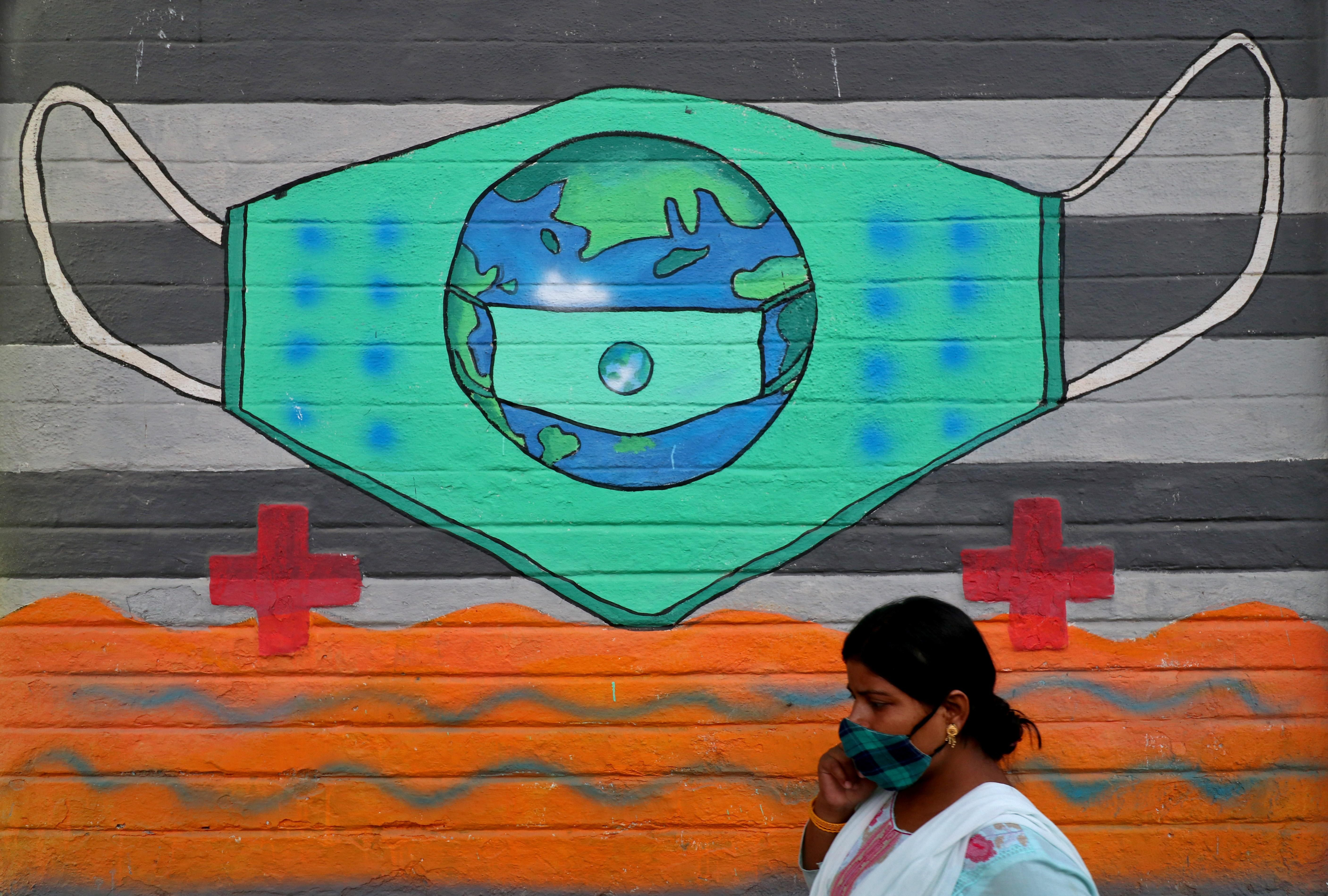 A woman wearing a protective face mask walks past a graffiti on a wall, amidst the spread of the coronavirus disease (COVID-19), in Mumbai, India, March 25, 2021.
