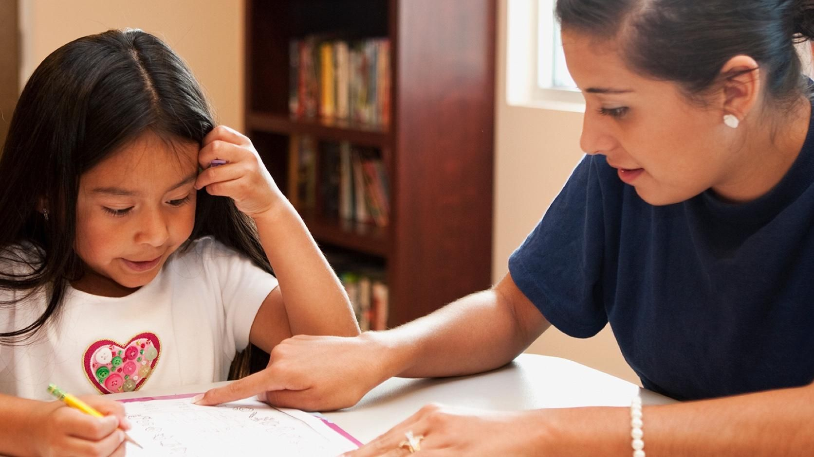 A young student gets help from a teacher. Critical support for teachers.