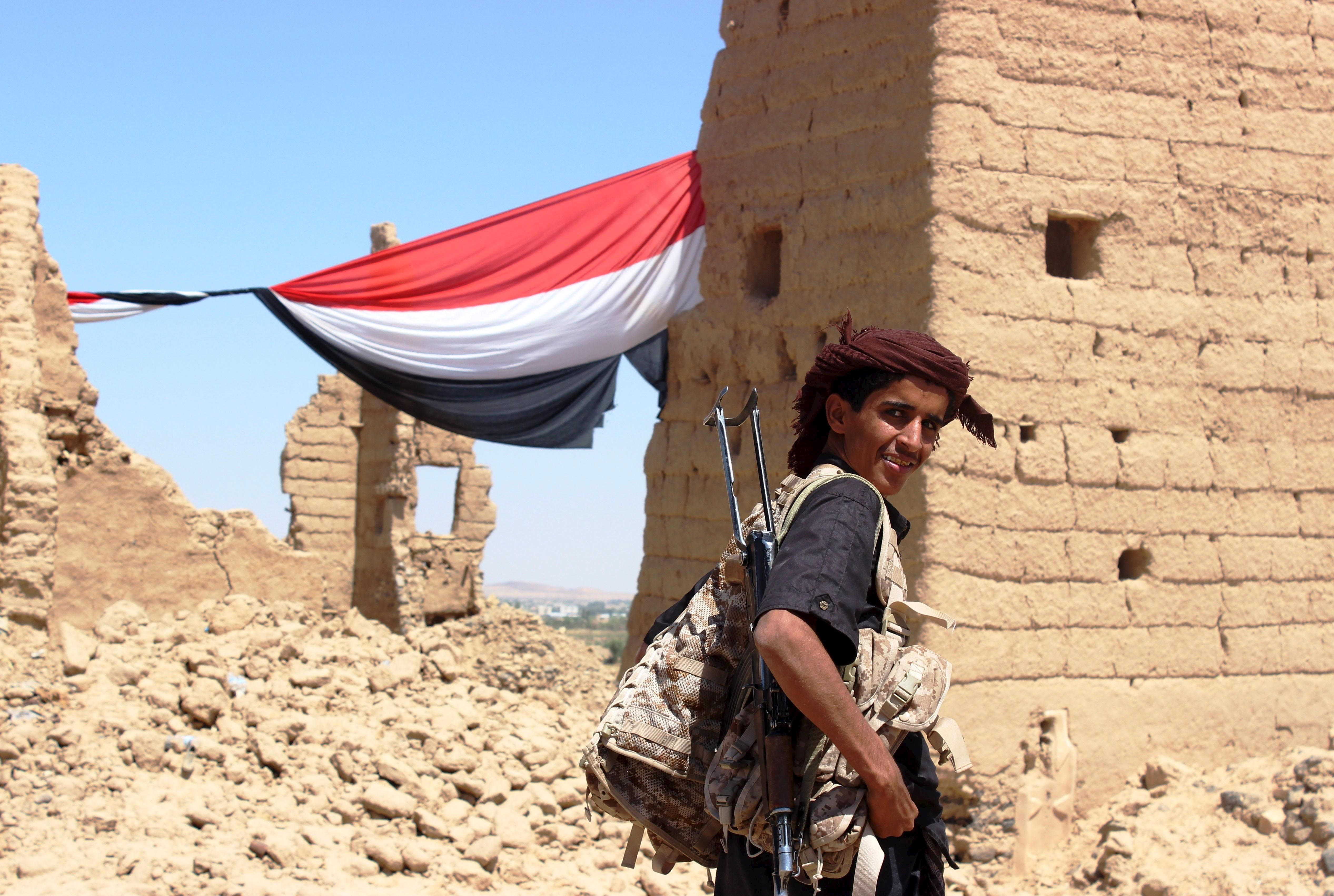 """A young Yemeni fighter shouldering a weapon smiles at the camera near Marib, Yemen October 16, 2015. Marib is a city that is heavily armed even by the standards of Yemen, where the ready availability of weapons helped start civil war and is now preventing anyone coming out on top. Yemenis often say there are three guns for every person, a boast that has become an urgent concern in a country where the United Nations says the humanitarian situation is """"critical""""."""