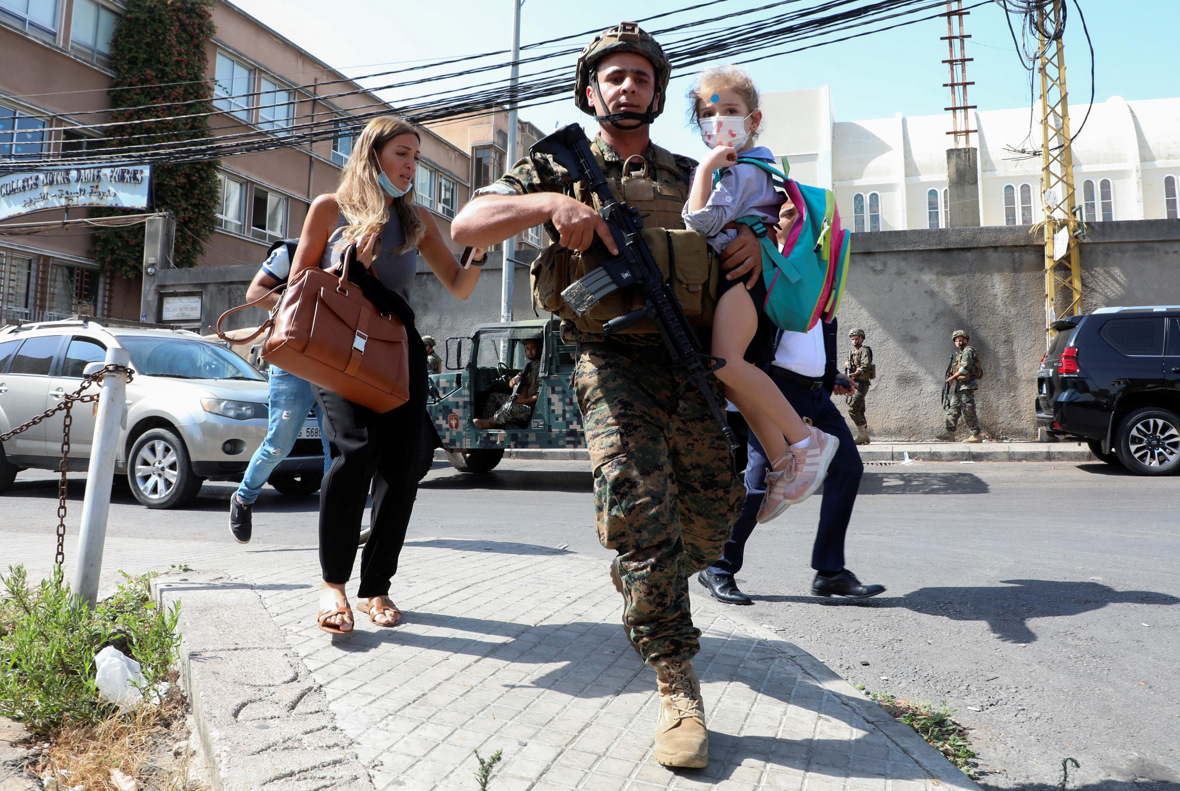 An army soldier carries a schoolchild as civilians flee after gunfire erupted at a site near a protest that was getting underway against Judge Tarek Bitar, who is investigating last year's port explosion, in Beirut, Lebanon October 14, 2021.