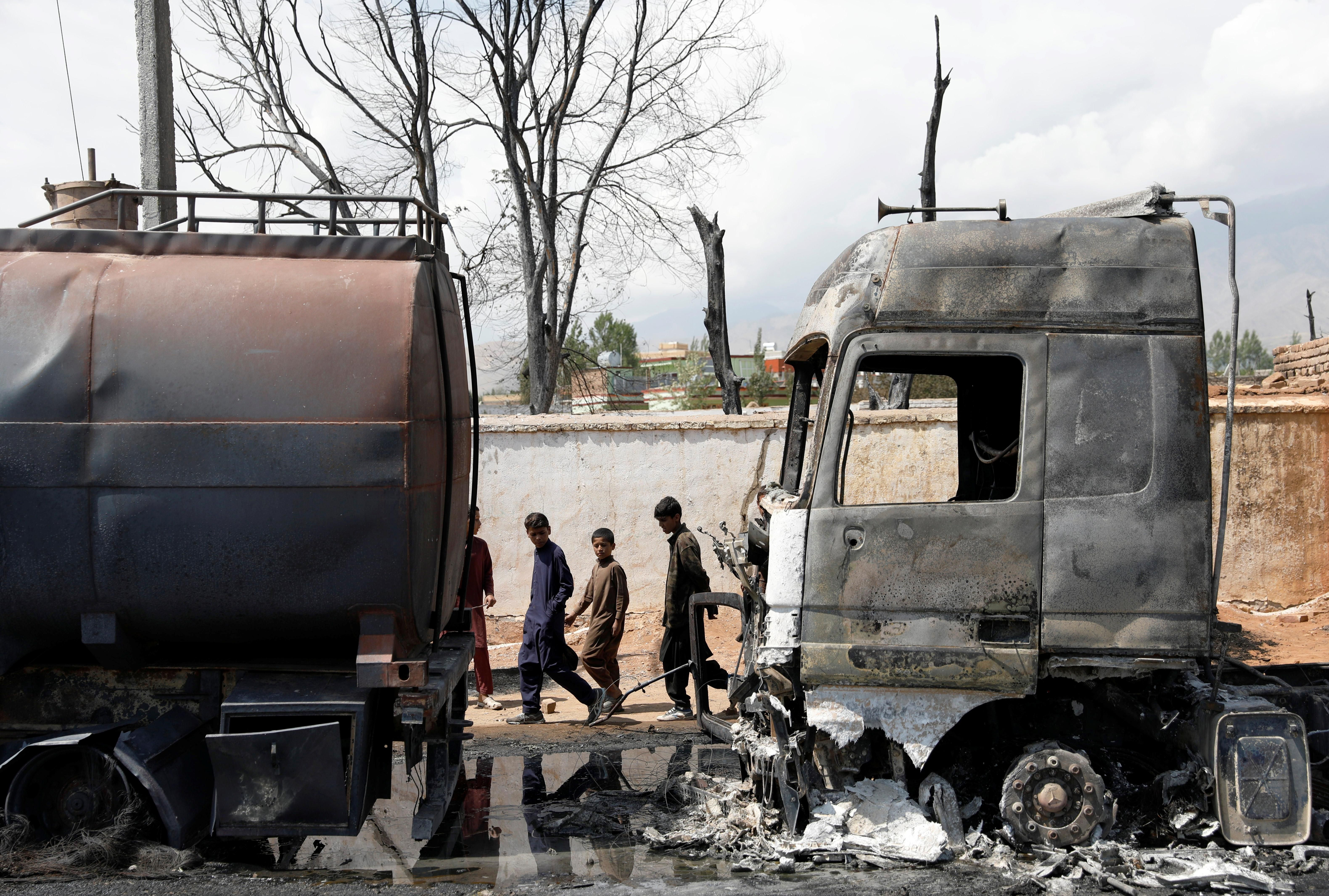 Boys walk past burnt fuel tankers after an overnight fire, on the outskirts of Kabul, Afghanistan May 2, 2021.