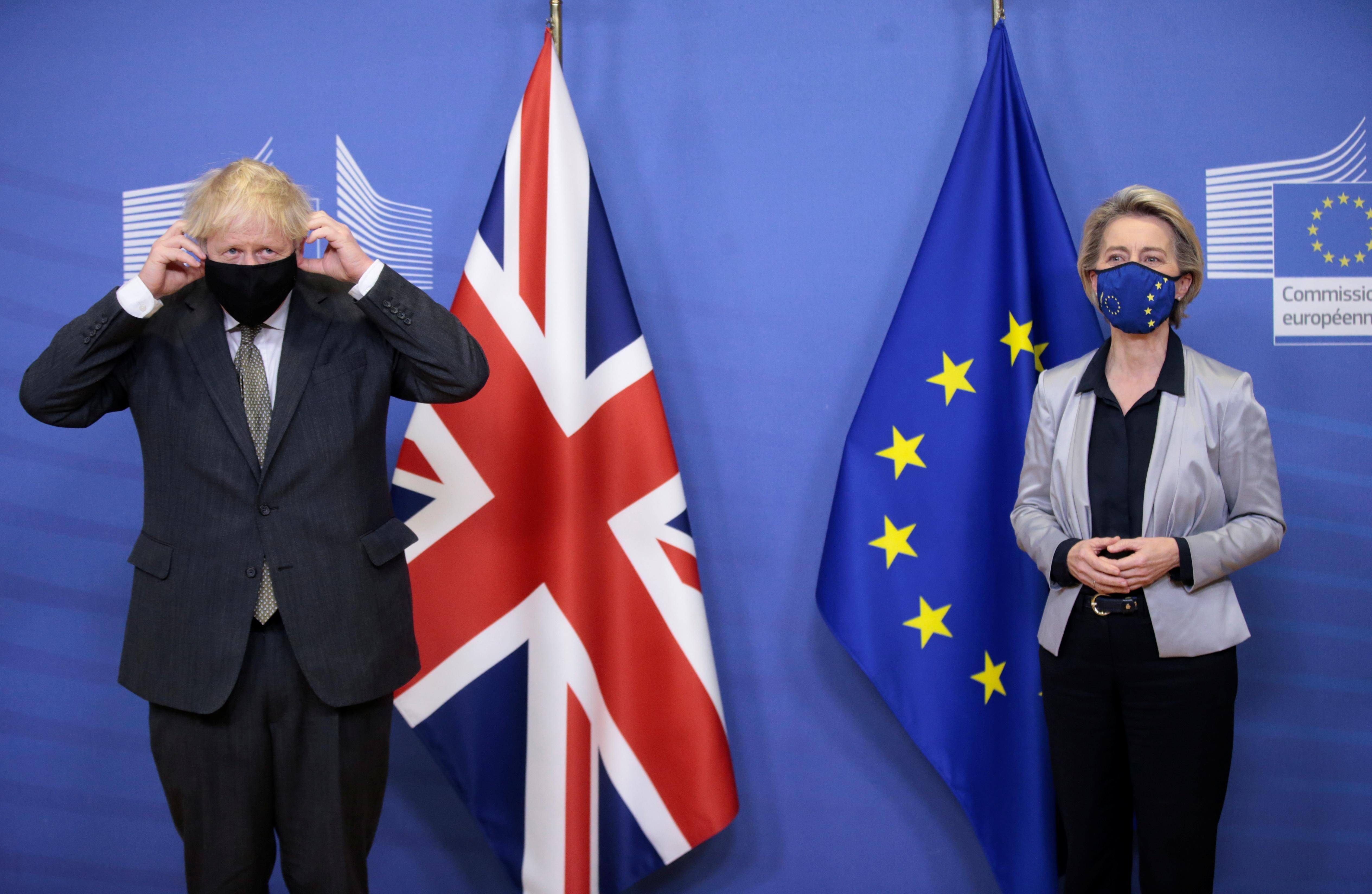 British Prime Minister Boris Johnson adjusts his face mask as he meets European Commission President Ursula von der Leyen in Brussels, Belgium December 9, 2020.