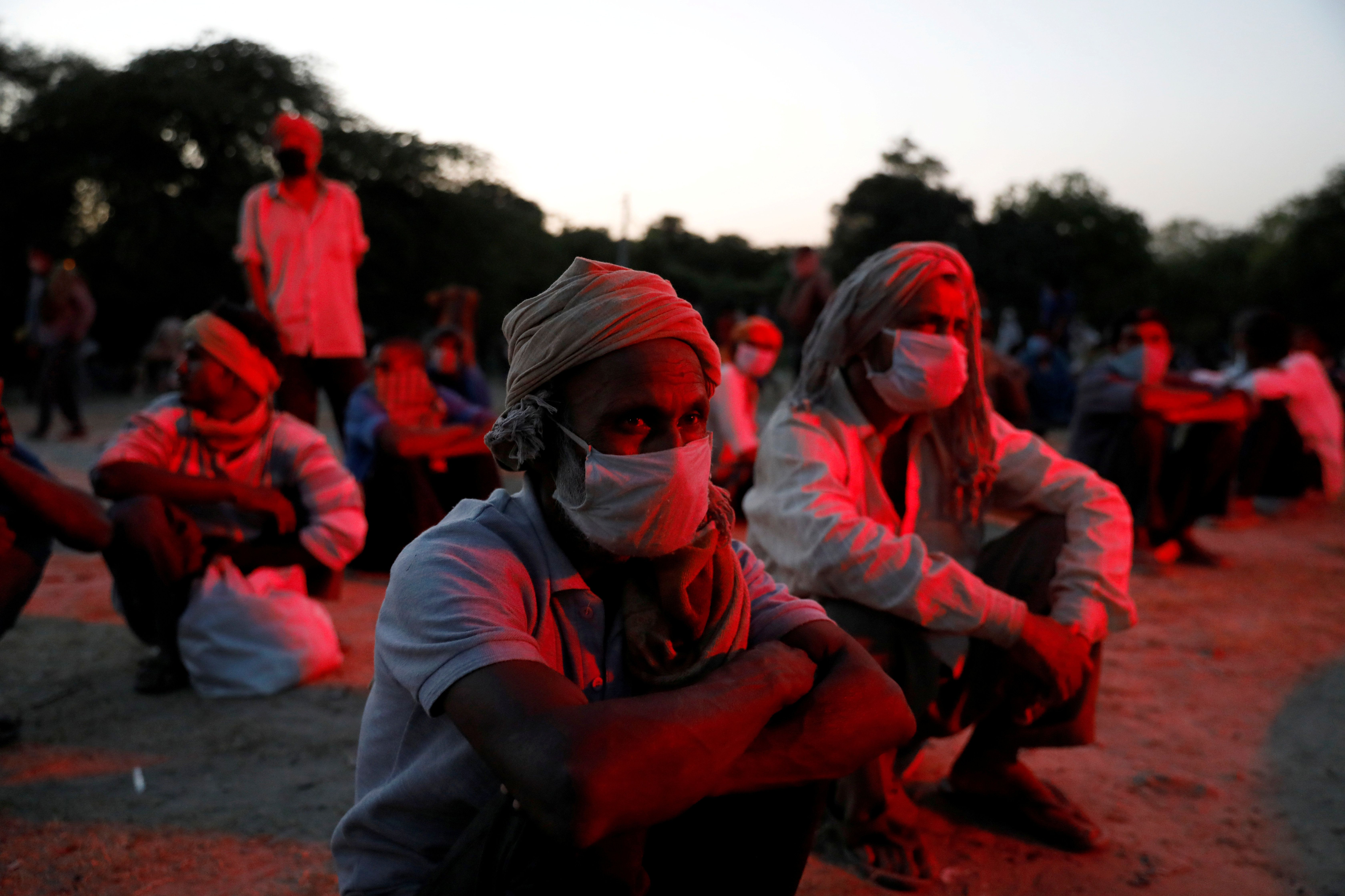 Daily wage workers and homeless people wearing face masks on the banks of Yamuna river in India. Reuters
