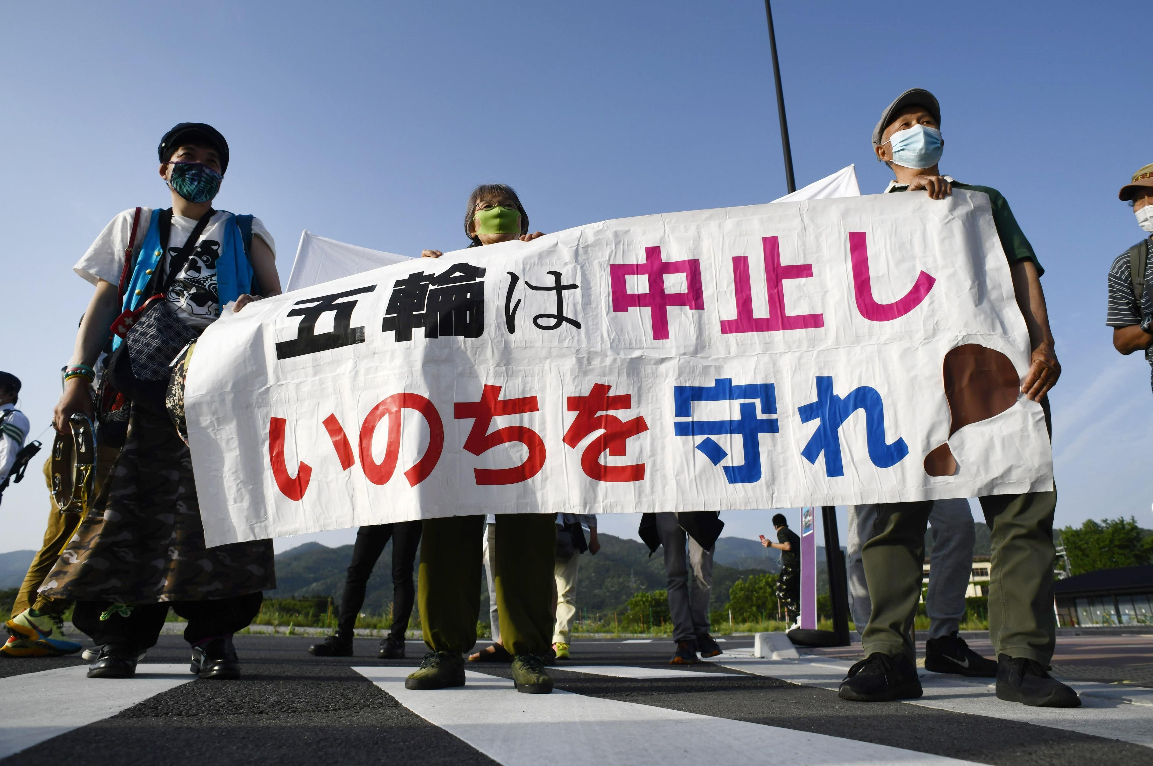 Demonstrators stage a protest in front of Sanga Stadium in the Kyoto Prefecture city of Kameoka, western Japan, on May 25, 2021, against the Tokyo Olympics amid the coronavirus pandemic. The Olympic torch relay was held inside the stadium the same day
