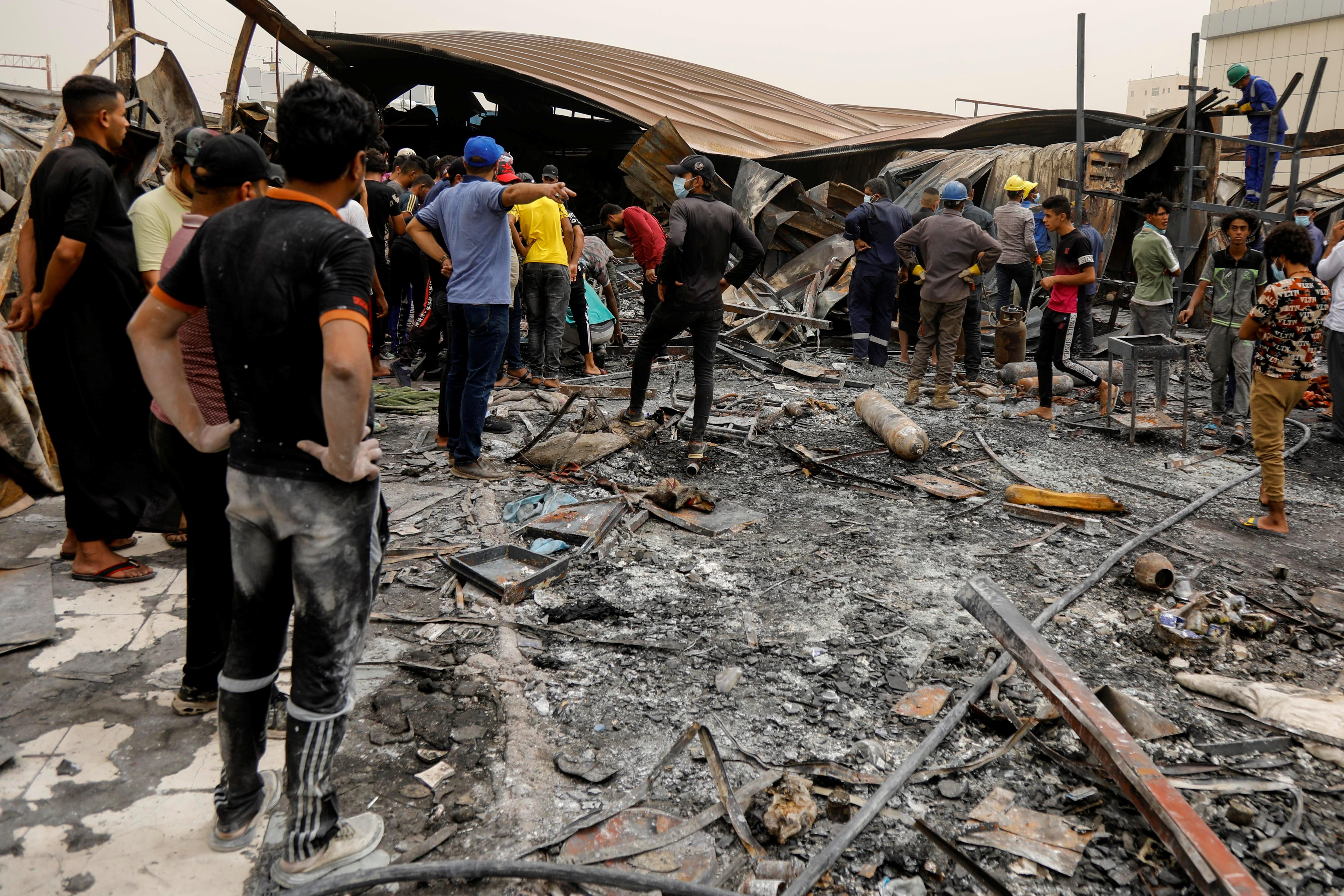 eople gather as they inspect the damage at al-Hussain coronavirus hospital where a fire broke out, in Nassiriya, Iraq, July 13, 2021.