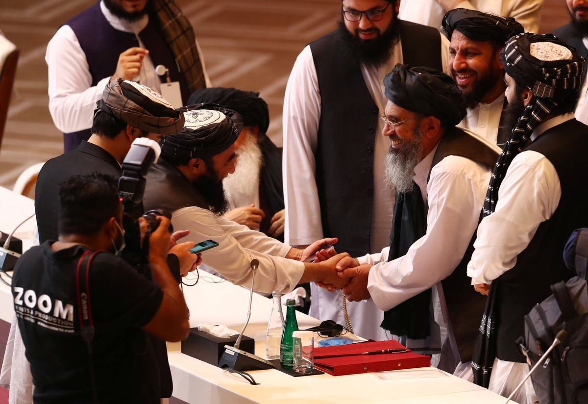 Taliban delegates shake hands during talks between the Afghan government and Taliban insurgents in Doha, Qatar