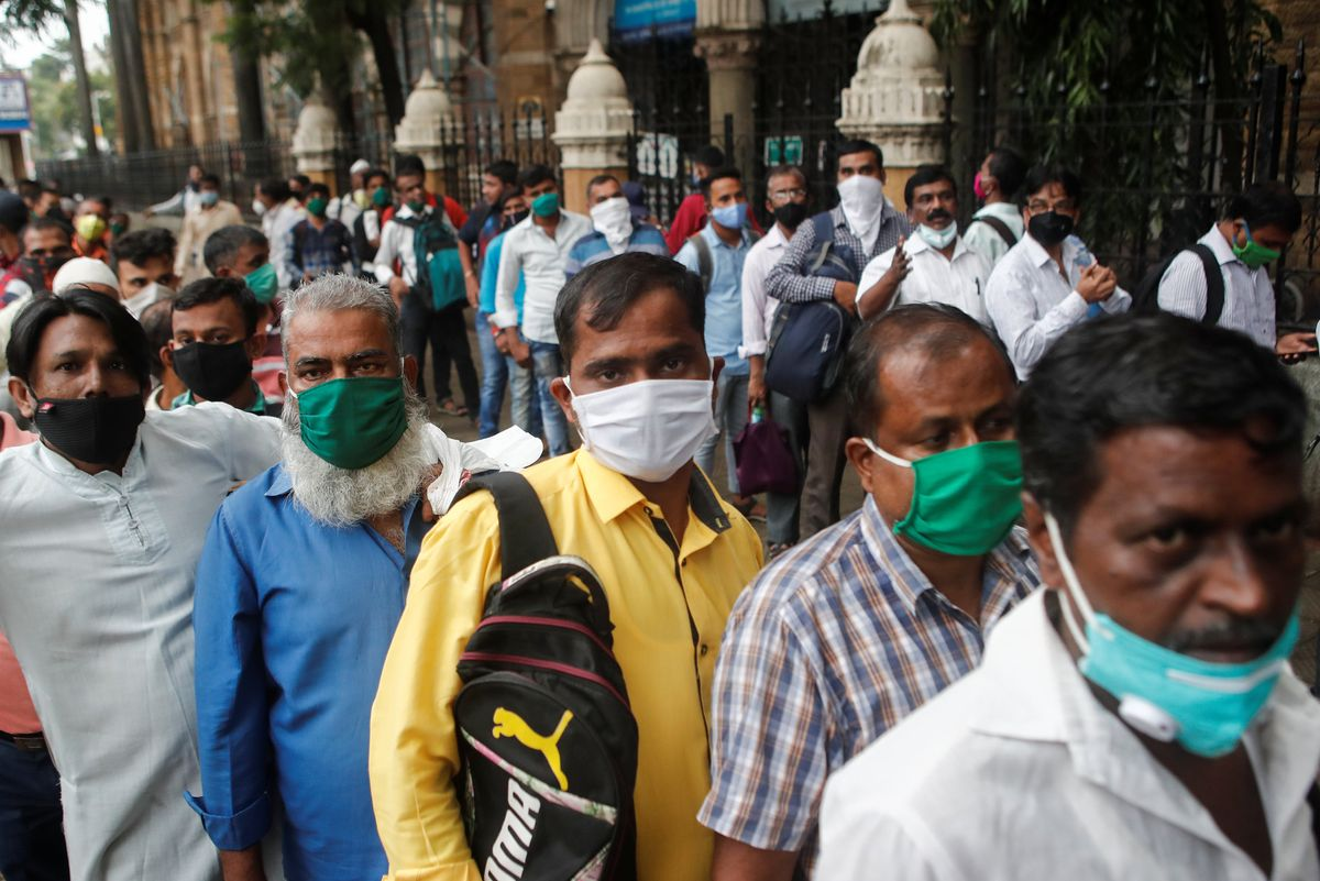 People wait in line to board a bus amidst the spread of the coronavirus disease (COVID-19) in Mumbai