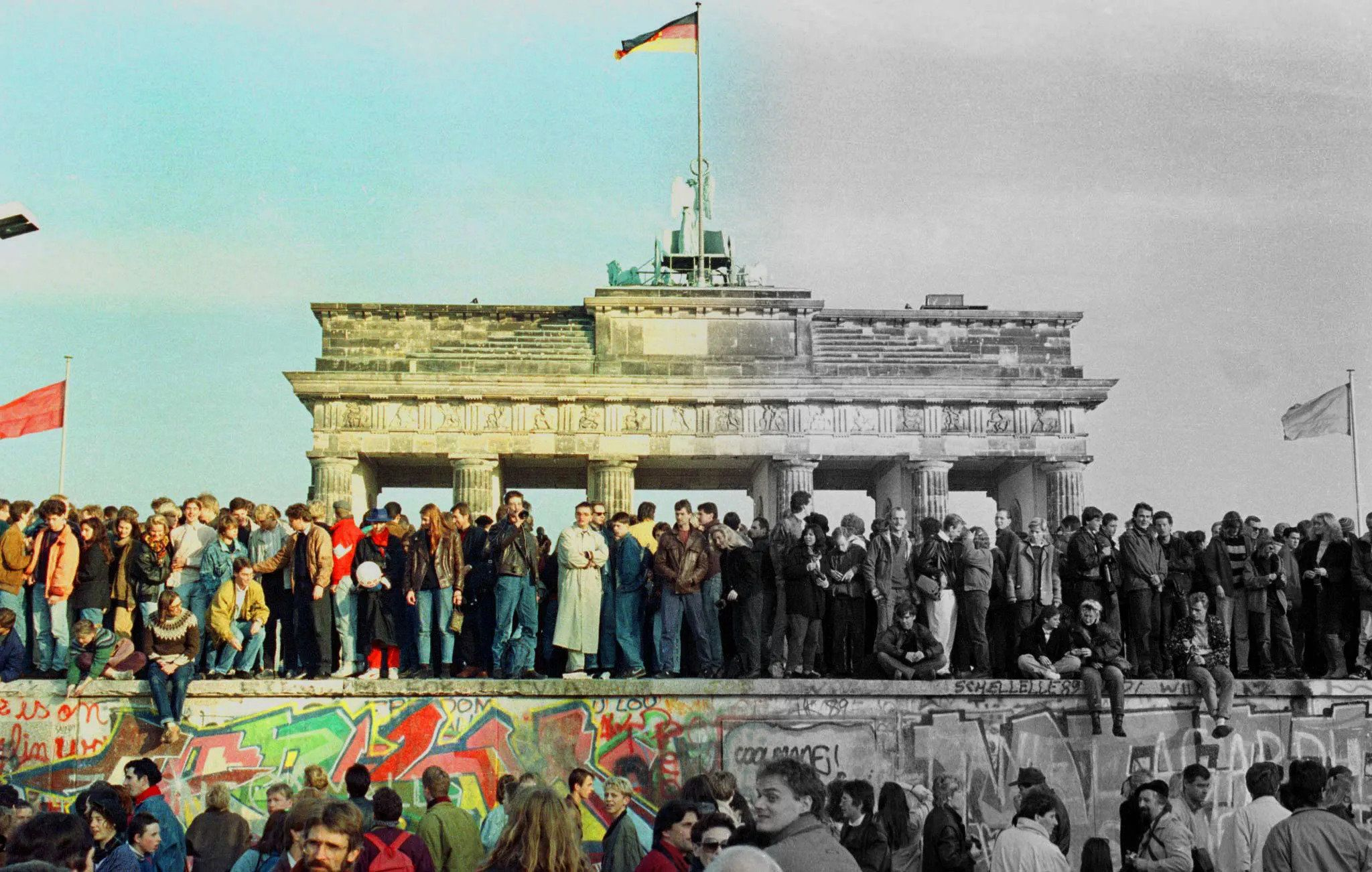 The Brandenburg Gate with a German flag during the period of reunification in Berlin, Germany