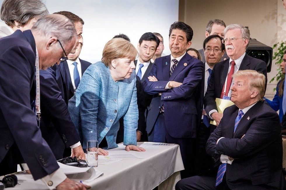 President Donald Trump seated surrounded by foreign leaders including Germany's Angela Merkel, Japan's Shinzo Abe and France's Emmanuel Macron
