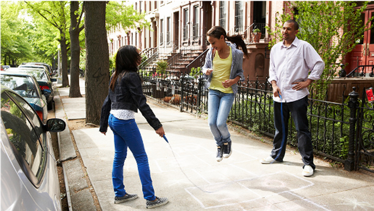 photograph of a girl skipping rope on a tree-lined city sidewalk, with a female and male handling the jumprope