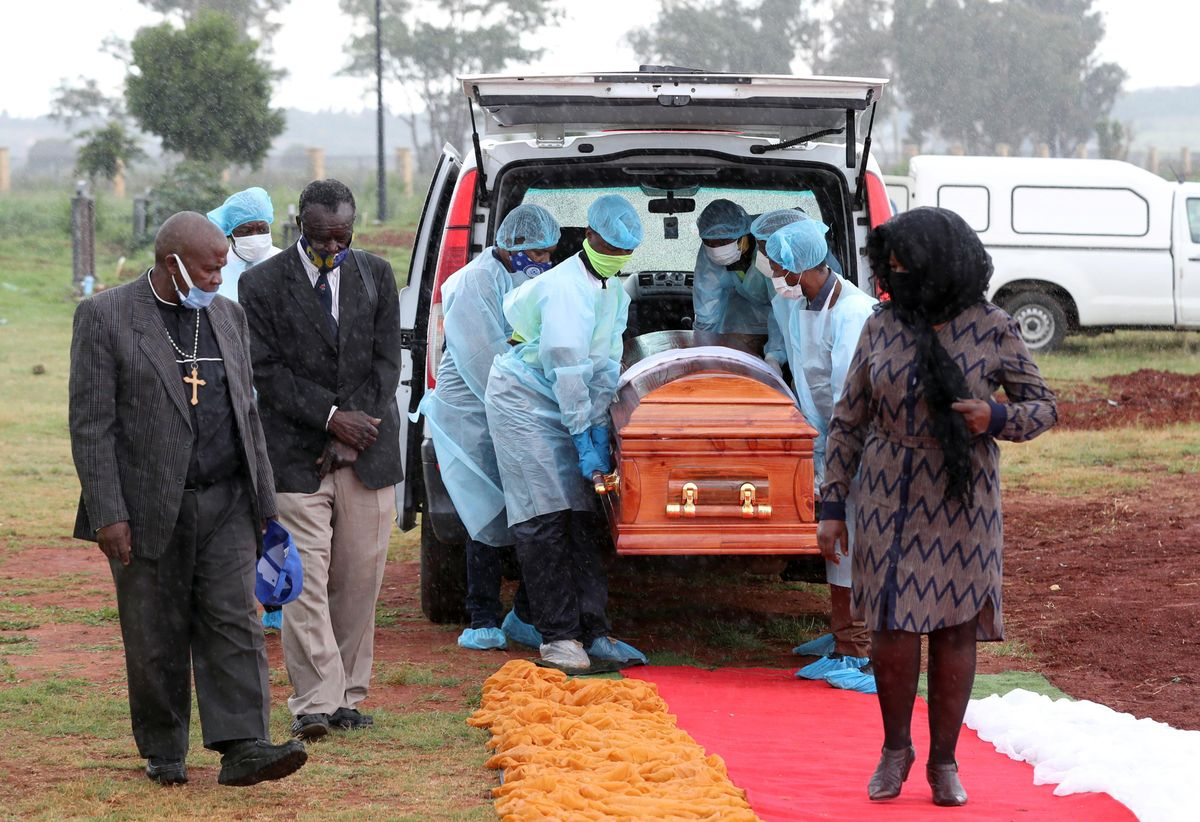 Funeral workers wearing personal protective equipment carry a casket during the burial of a COVID-19 victim, amid a nationwide coronavirus disease (COVID-19) lockdown, at the Olifantsvlei cemetery, south-west of Joburg, South Africa January 6, 2021