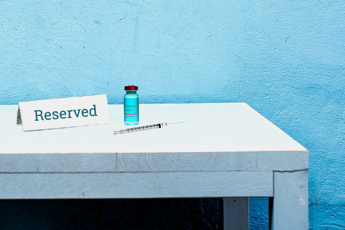 """COVID vaccine vile and needle next to a placard that says """"reserved"""""""