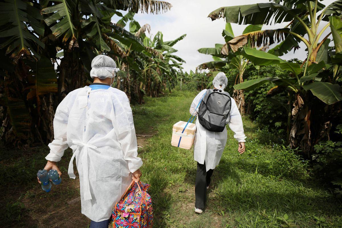 Municipal health workers walk along the Solimoes river banks, where Ribeirinhos (river dwellers) live, before applying the AstraZeneca/Oxford vaccine for the coronavirus disease (COVID-19) to the residents, in Manacapuru, Amazonas state, Brazil, February 1, 2021.