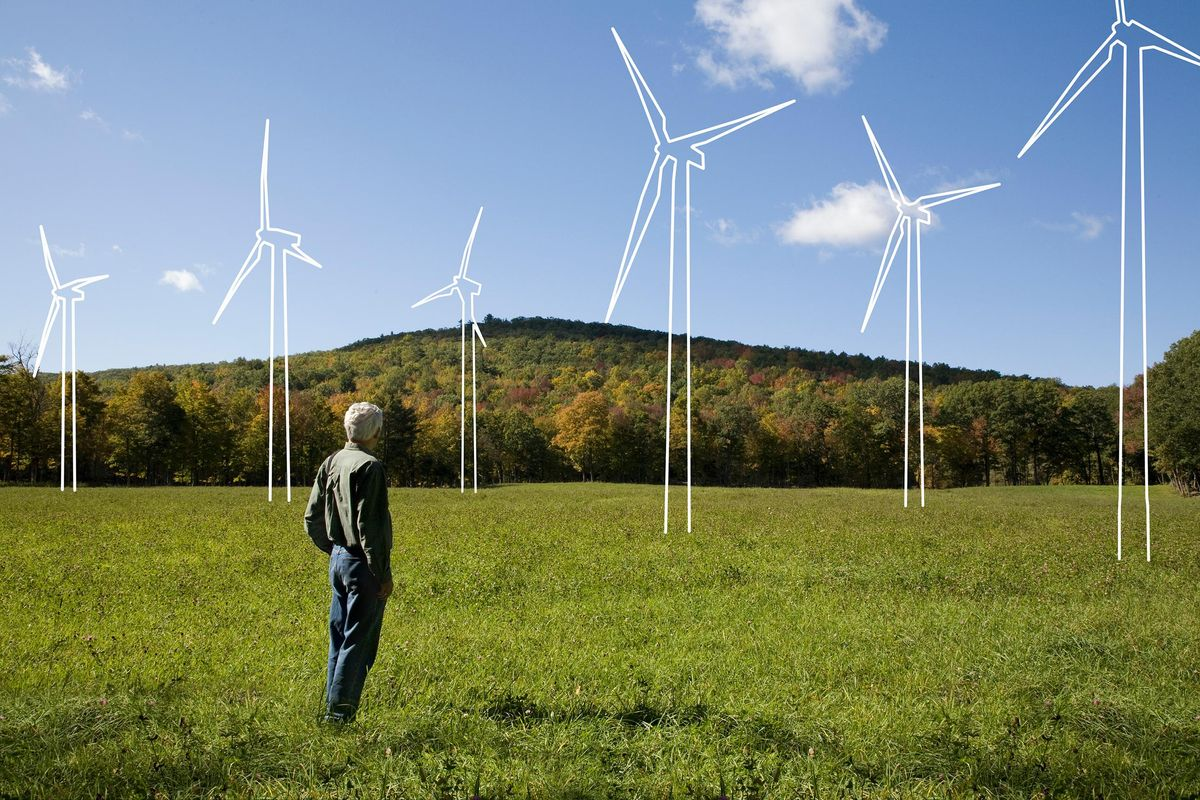 A man looks at a windmill farm. Bank of America to make a $1 trillion investment in sustainability by 2030