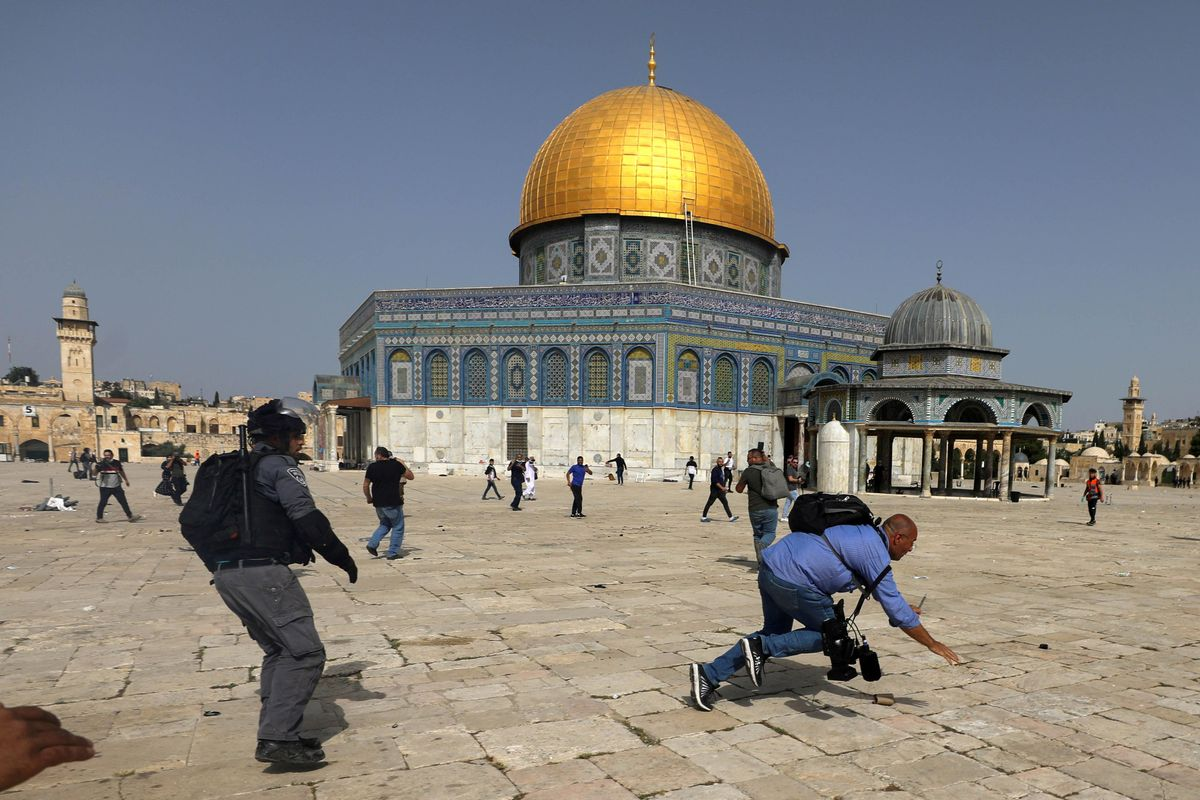 A camera operator falls as an Israeli police officer runs after him during clashes with Palestinians at the compound that houses Al-Aqsa Mosque, known to Muslims as Noble Sanctuary and to Jews as Temple Mount, in Jerusalem's Old City, May 10, 2021