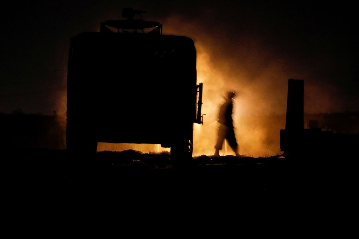 An Israeli soldier walks next to a military vehicle at a mobile artillery unit location on the Israeli side by the Israel border with Gaza May 16, 2021.