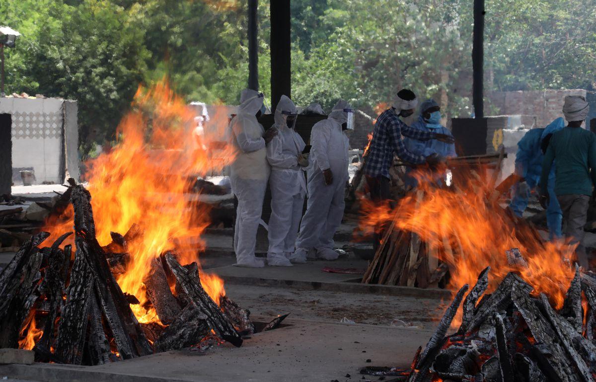 Relatives of coronavirus (Covid-19) victims perform the last rites during a cremation at Mangolpuri crematorium ground in New Delhi.
