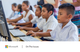 Image of a row of schoolchildren (boys and girls in white collared shirts) sitting in front of desktop computers and keyboards, with their hands on computer mouses