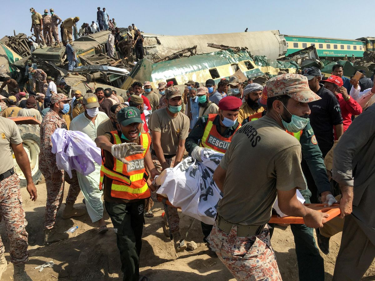 Paramilitary soldiers and rescue workers move a body of a man from the site following a collision between two trains in Ghotki, Pakistan June 7, 2021.
