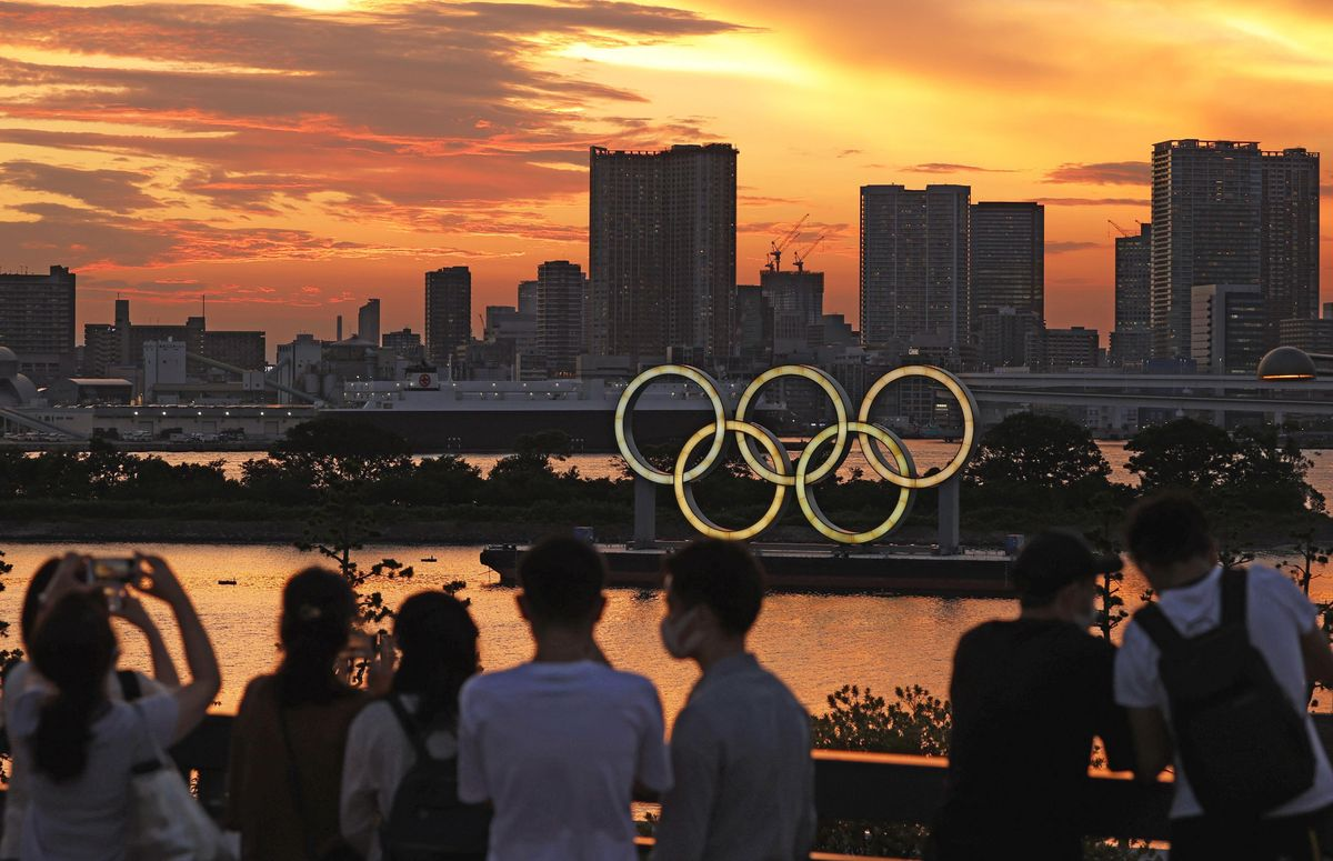 People look at an Olympics rings monument lit up after sunset in Tokyo on July 21, 2021, two days ahead of the Tokyo Olympics opening ceremony.