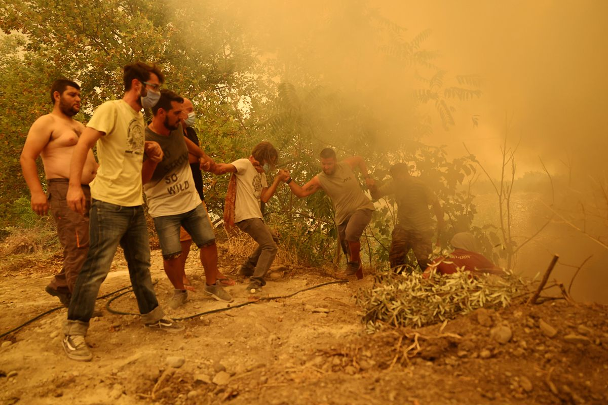 A man holding a hose is helped to climb a slope, as a wildfire burns in the village of Gouves, on the island of Evia, Greece, August 8, 2021.