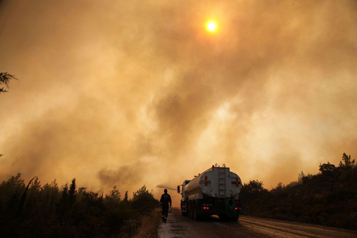 Firefighters extinguish a wildfire in the Mazi region near Bodrum, Turkey, August 2, 2021.