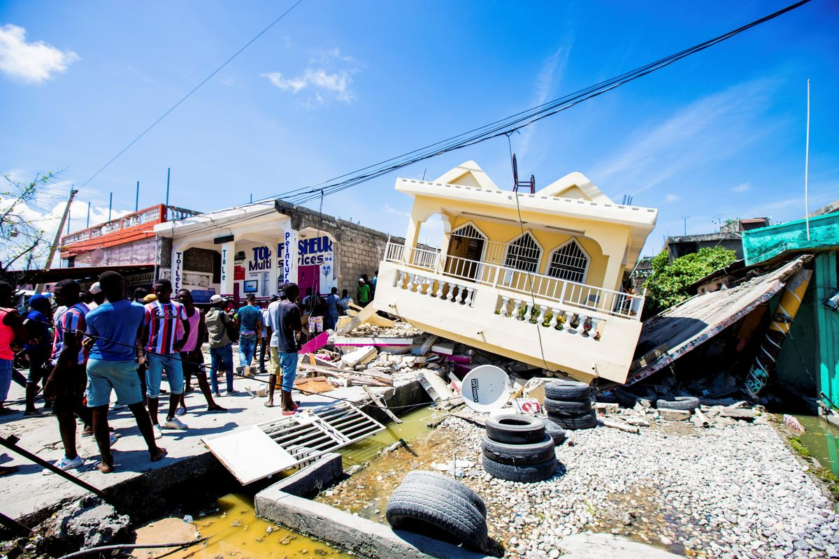 People stand next to a house destroyed following a 7.2 magnitude earthquake in Les Cayes, Haiti August 14, 2021.