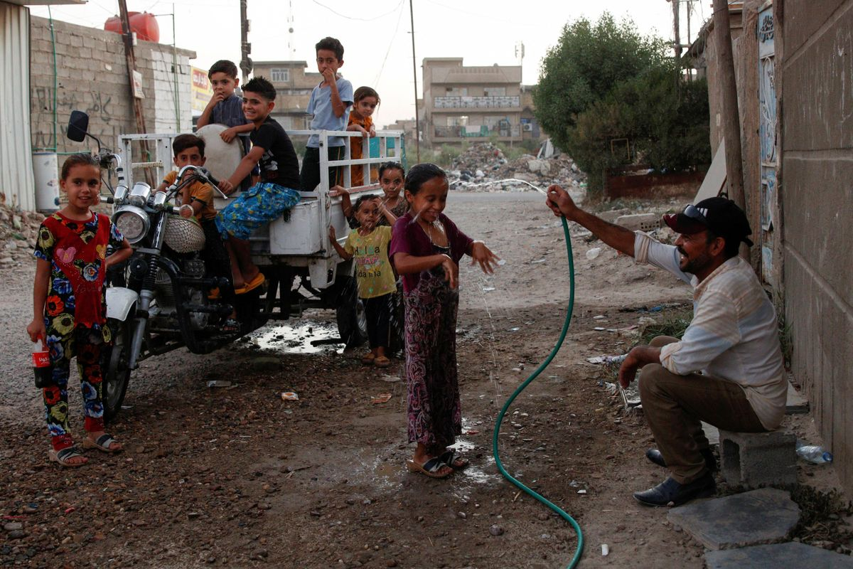 An Iraqi man sprays water on a girl in the street during a high temperature and power cut in Baghdad, Iraq July 3, 2021. Picture taken July 3, 2021