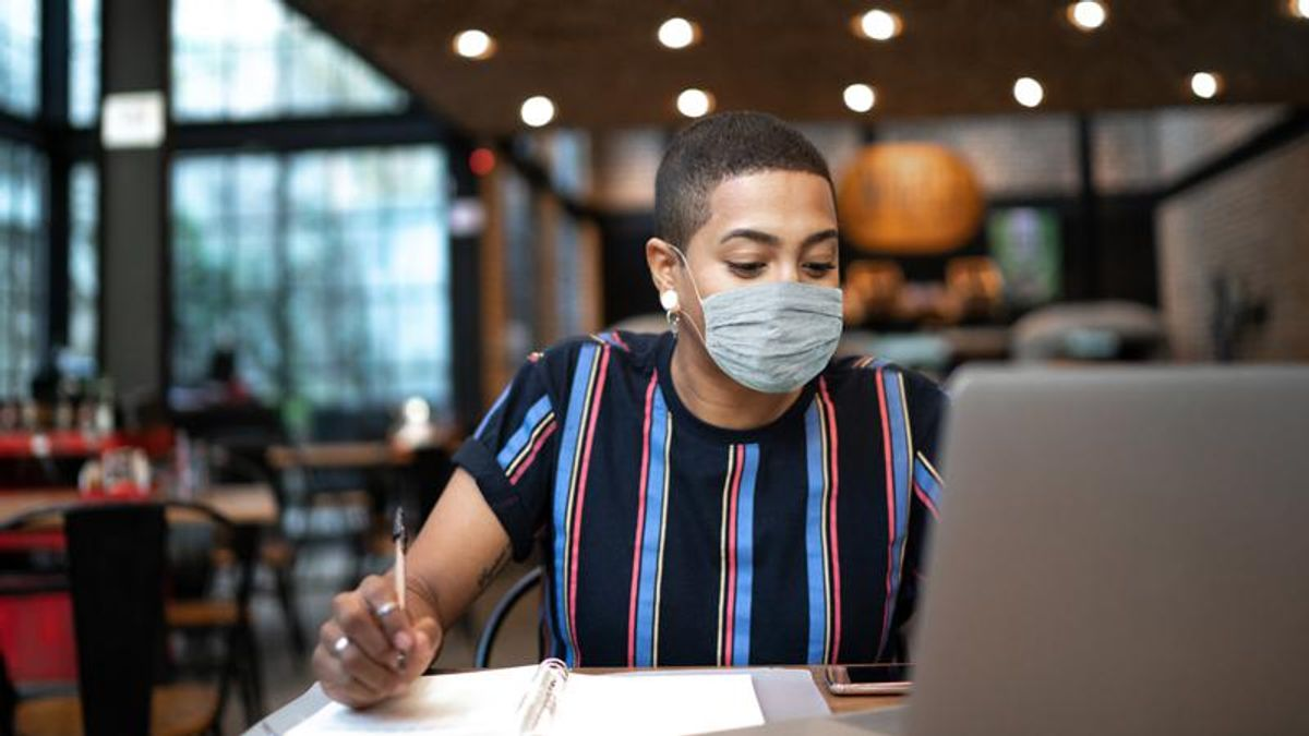 A person of color wearing a cloth mask working at a laptop