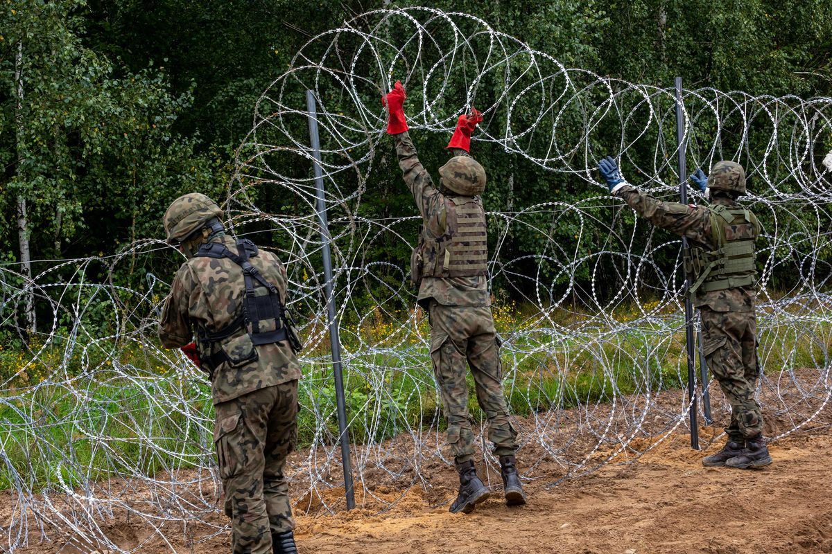 Polish Army Soldiers build a fence with concertina wire at the Belarusian border in order to stop immigrants from entering the country in Krynki, Poland on 27 August, 2021.